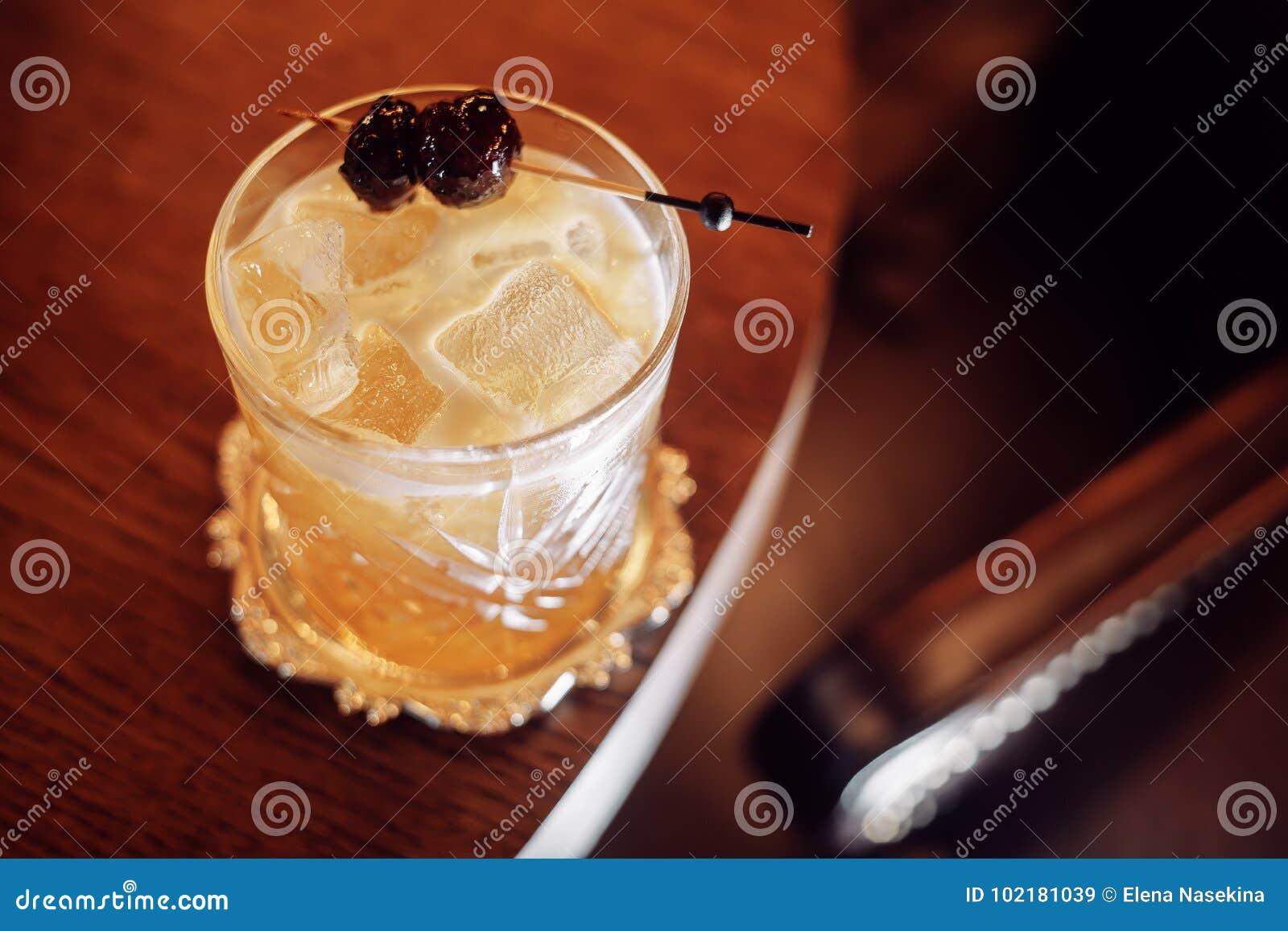 Rich gulnar coctailen med is och körsbäret på en pinne
