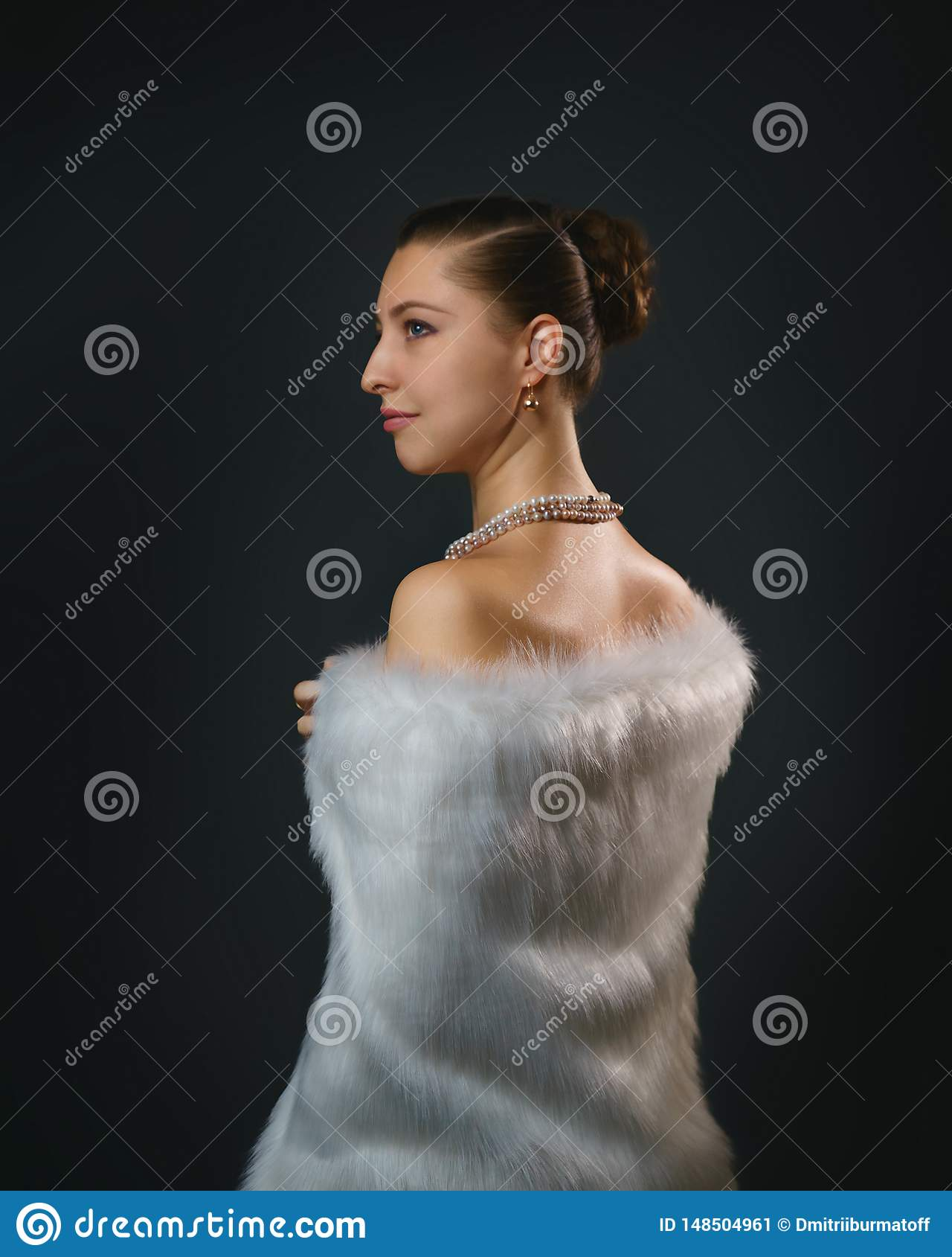 Rich lifestyle. Beautiful sexual woman wearing jewelery and white fur vest. Beauty, fashion