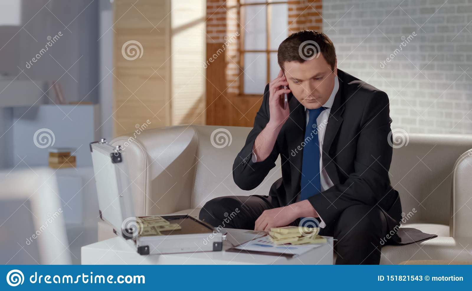 Rich man dealing with partner by phone, big money on table, profitable business