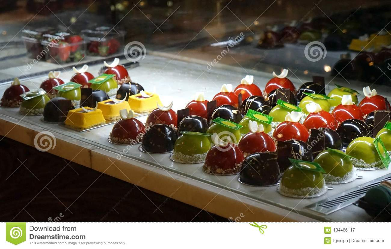 Rich variety of chocolate and jelly desserts in display window of pastry shop
