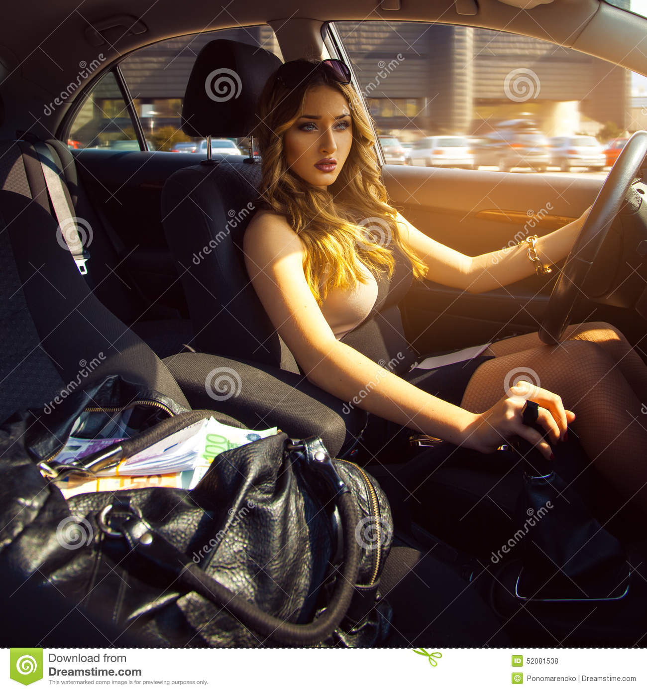Rich Young Girl Driving Car With Bag Full Of Money Stock Photo