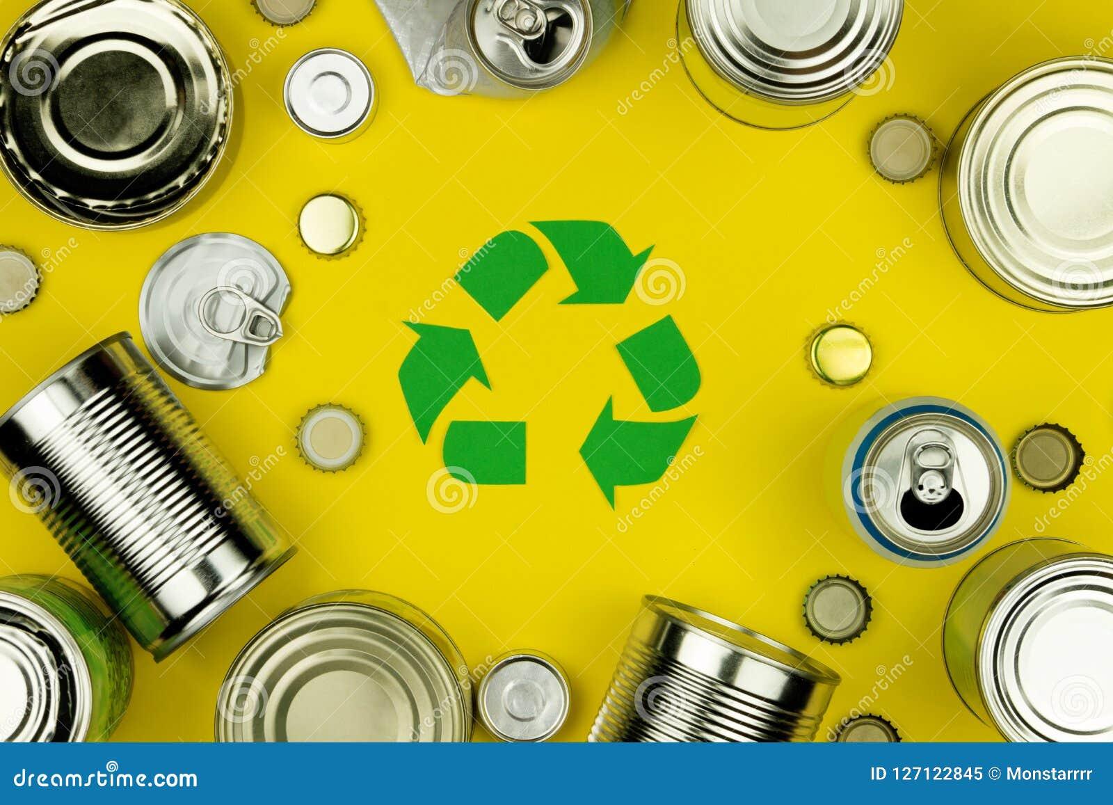 Ricicli il simbolo del segno di riutilizzazione con le latte di alluminio del metallo, le coperture, barattoli