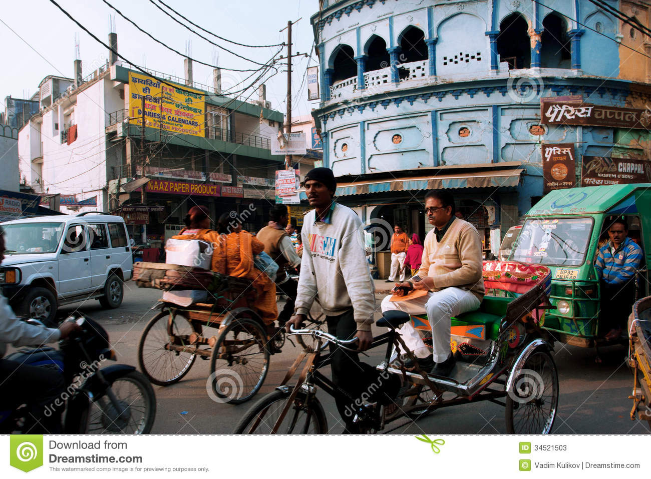 Rickshaw drives through the crowded street with many bikes in Lucknow, India