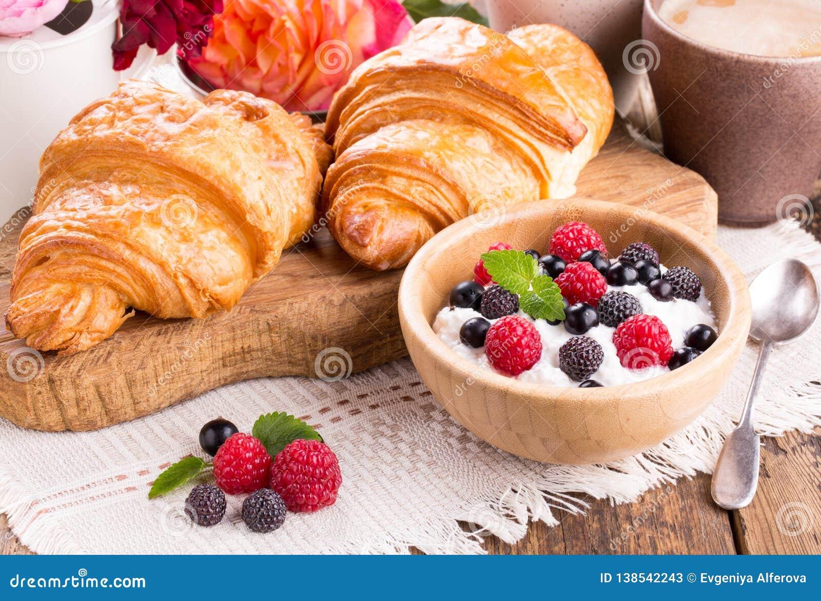 Ricotta con le bacche, la tazza di caffè ed i croissant freschi