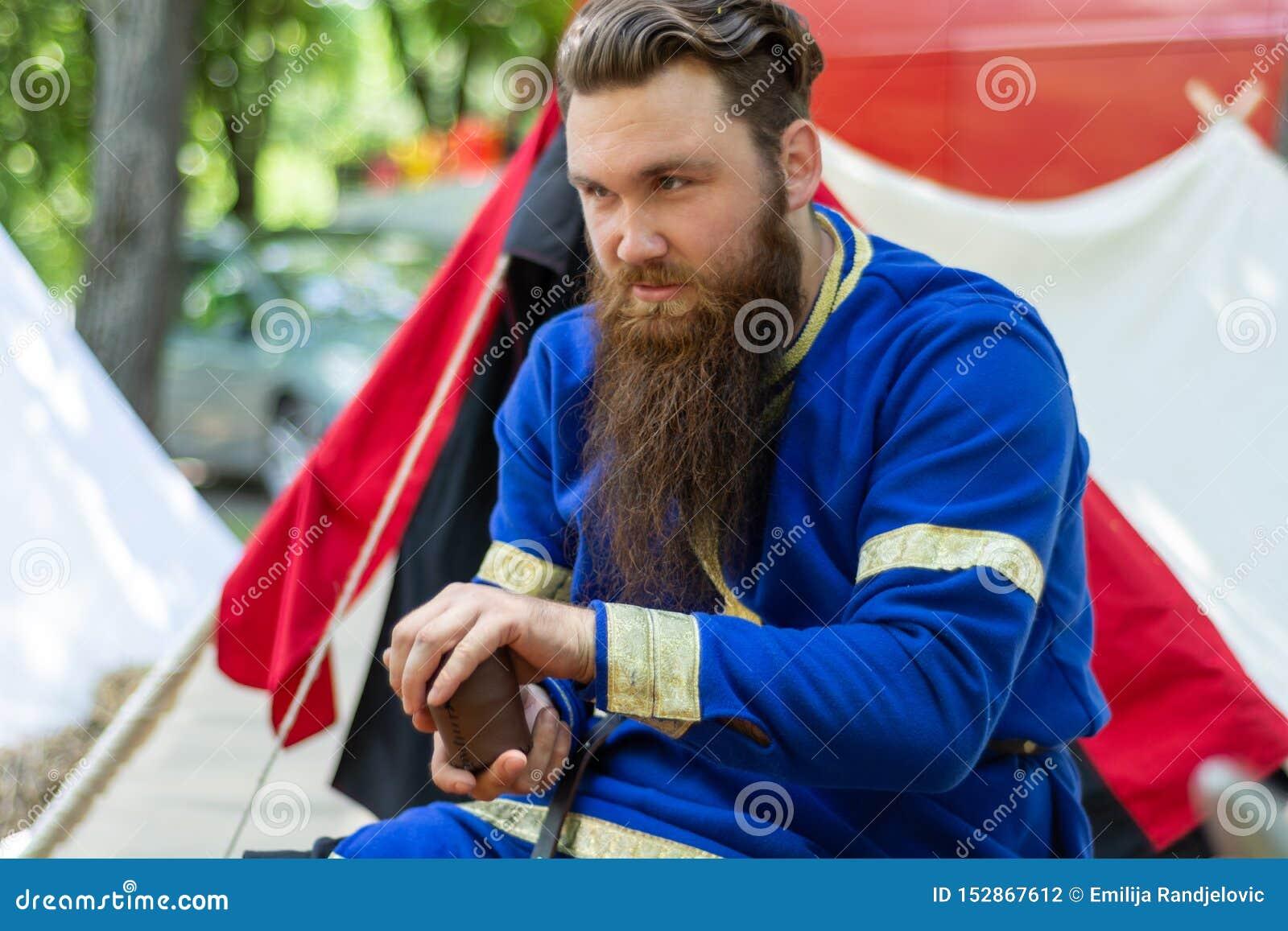 Riddaren med ett skägg i en blå traditionell dräkt sitter framme av tältet och spelar en gammal tärninglek