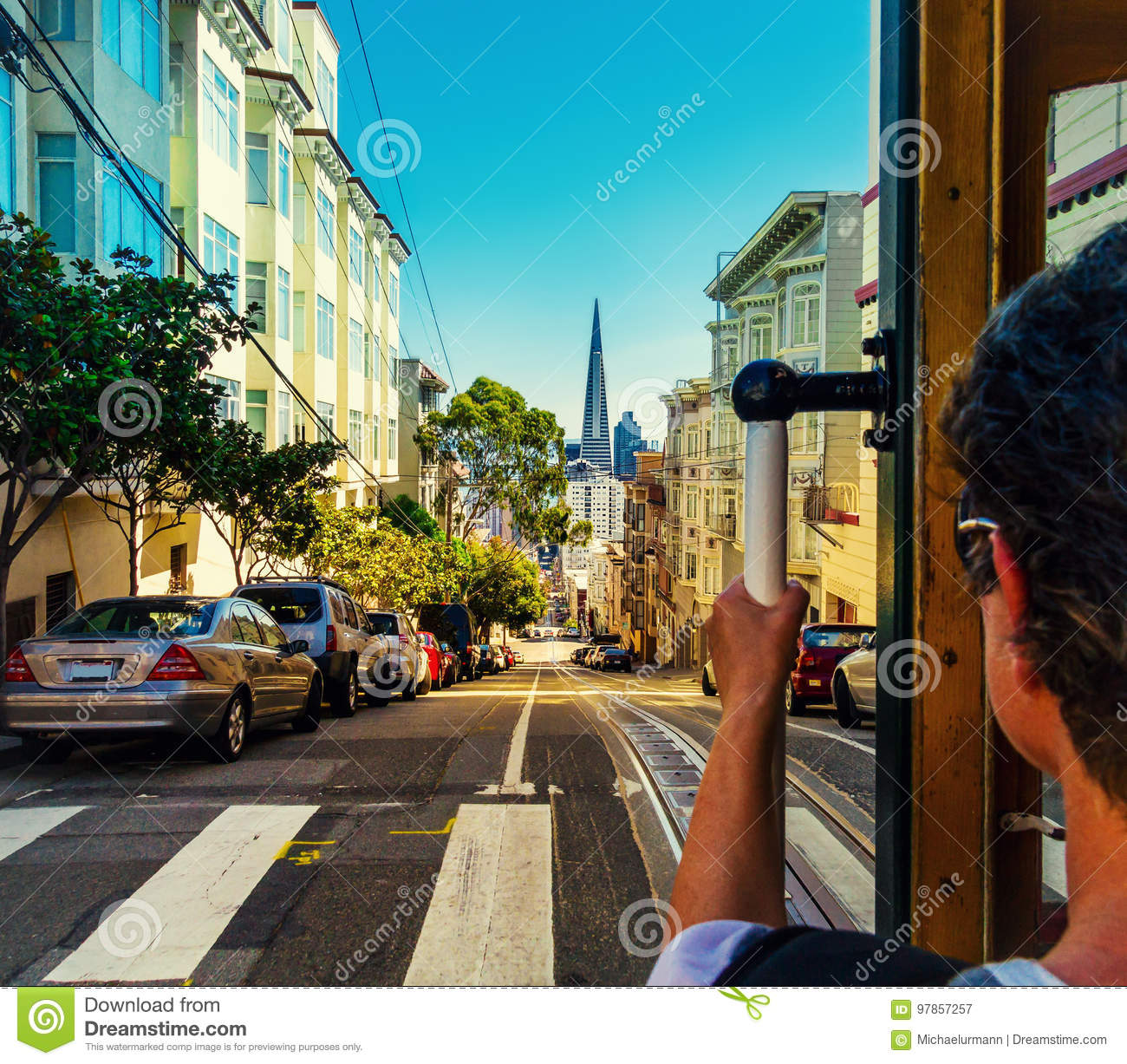 Ride with the cable car in San Francisco. Picture shows a person riding the famous MUNI train on Powell-Mason line.