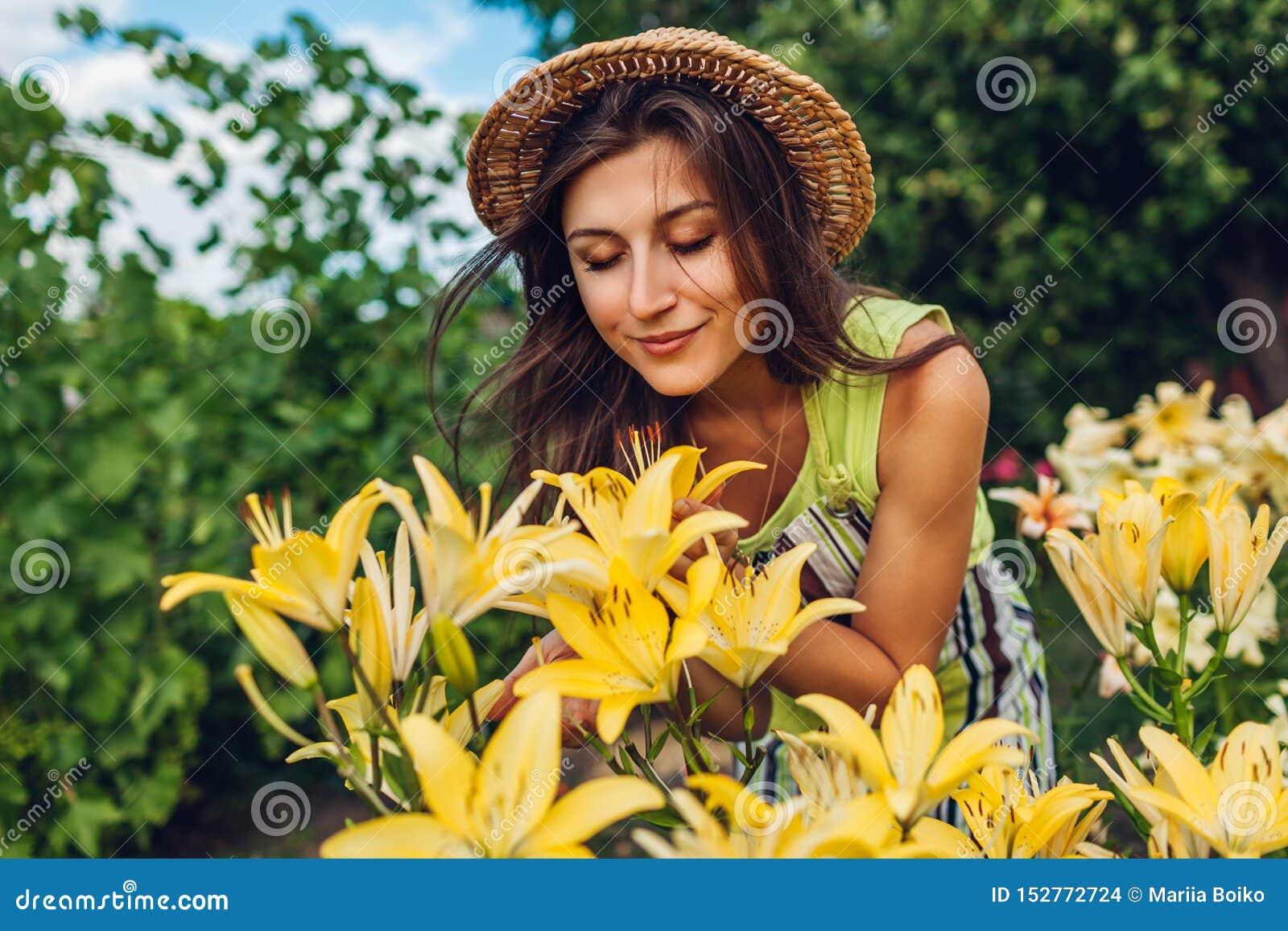 Riechende Blumen der jungen Frau im Garten Gärtner, der um Lilien sich kümmert Im Garten arbeitenkonzept
