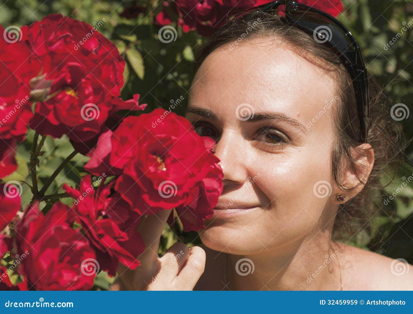Riechende Rosen der jungen Frau