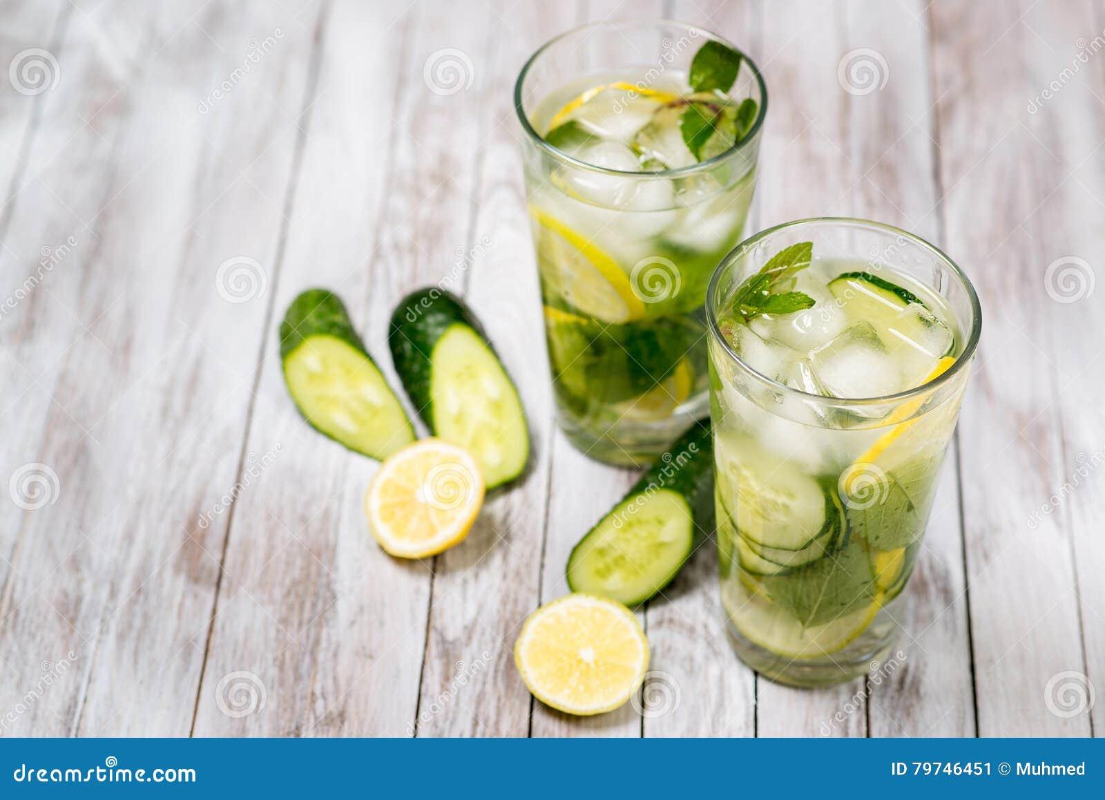 Riegue con el limón, la menta y el pepino en fondo ligero de madera Detox del agua