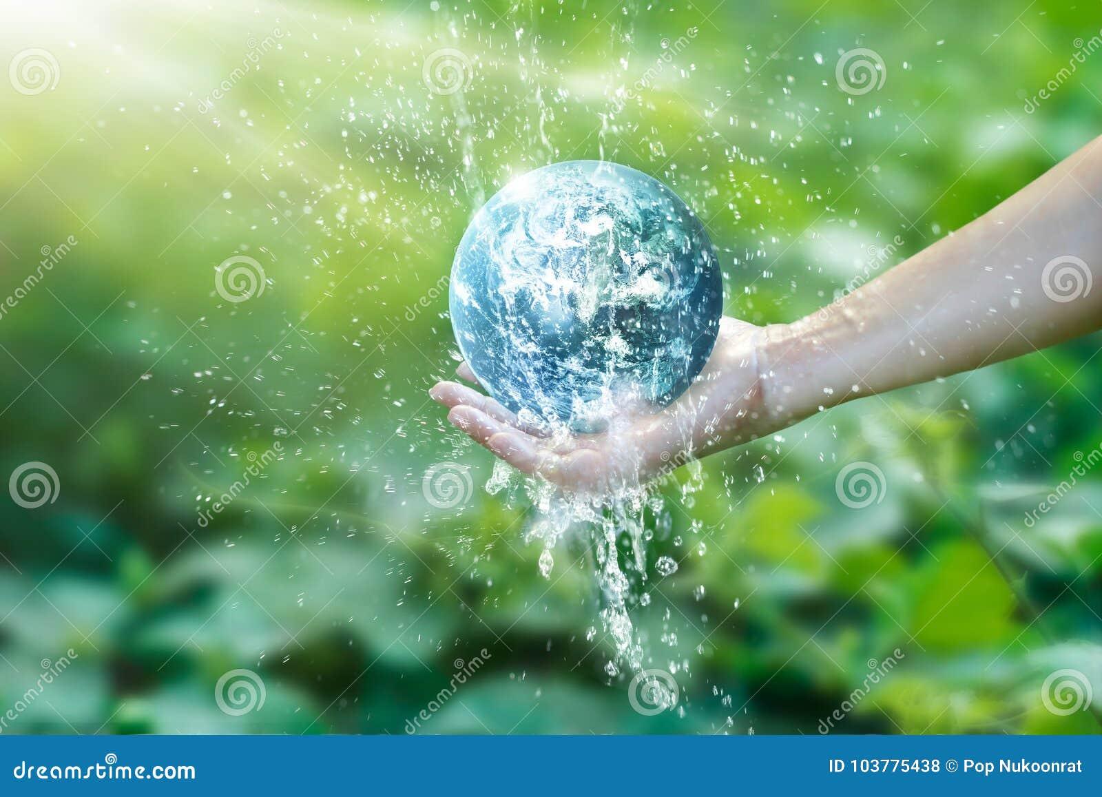 Riegue la colada en la tierra del planeta colocada en la mano humana