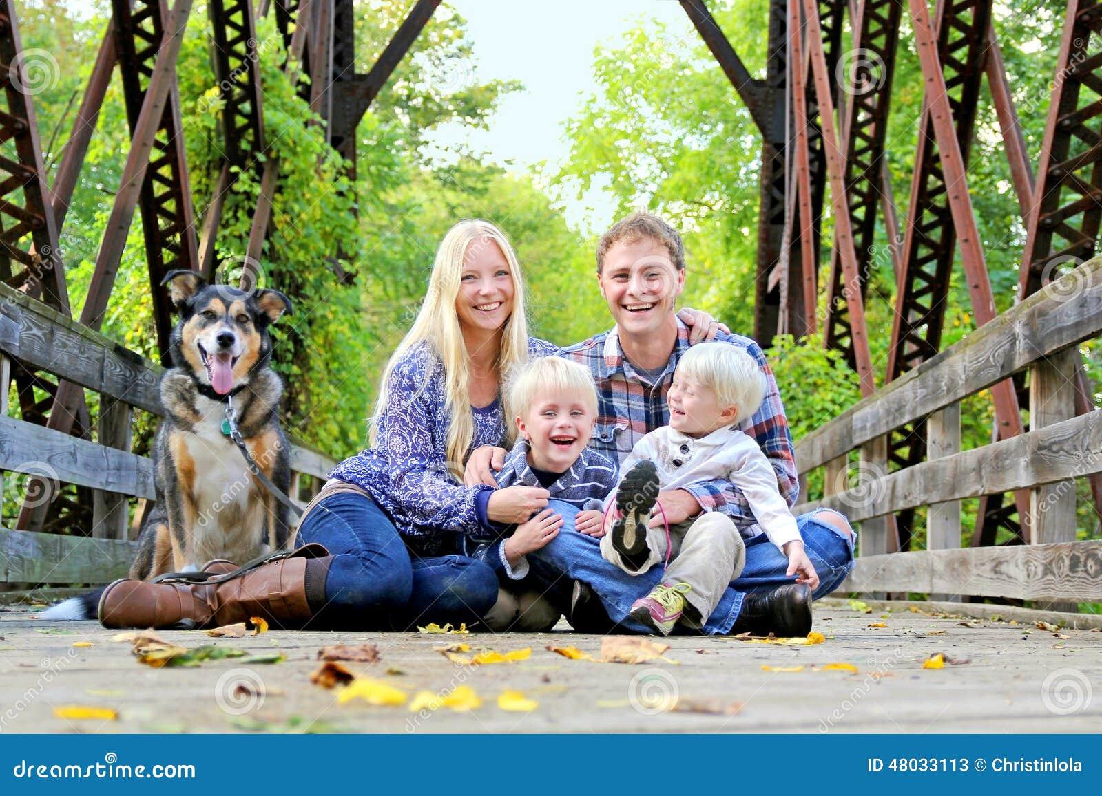 Riendo, familia feliz que se sienta en el puente en Autumn Forest