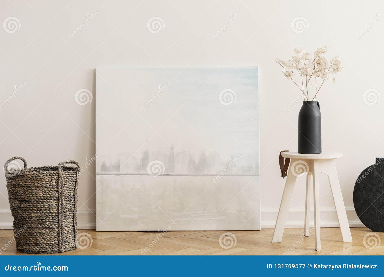 Rieten mand en houten lijst met zwarte vaas met bloemen, echte foto met model
