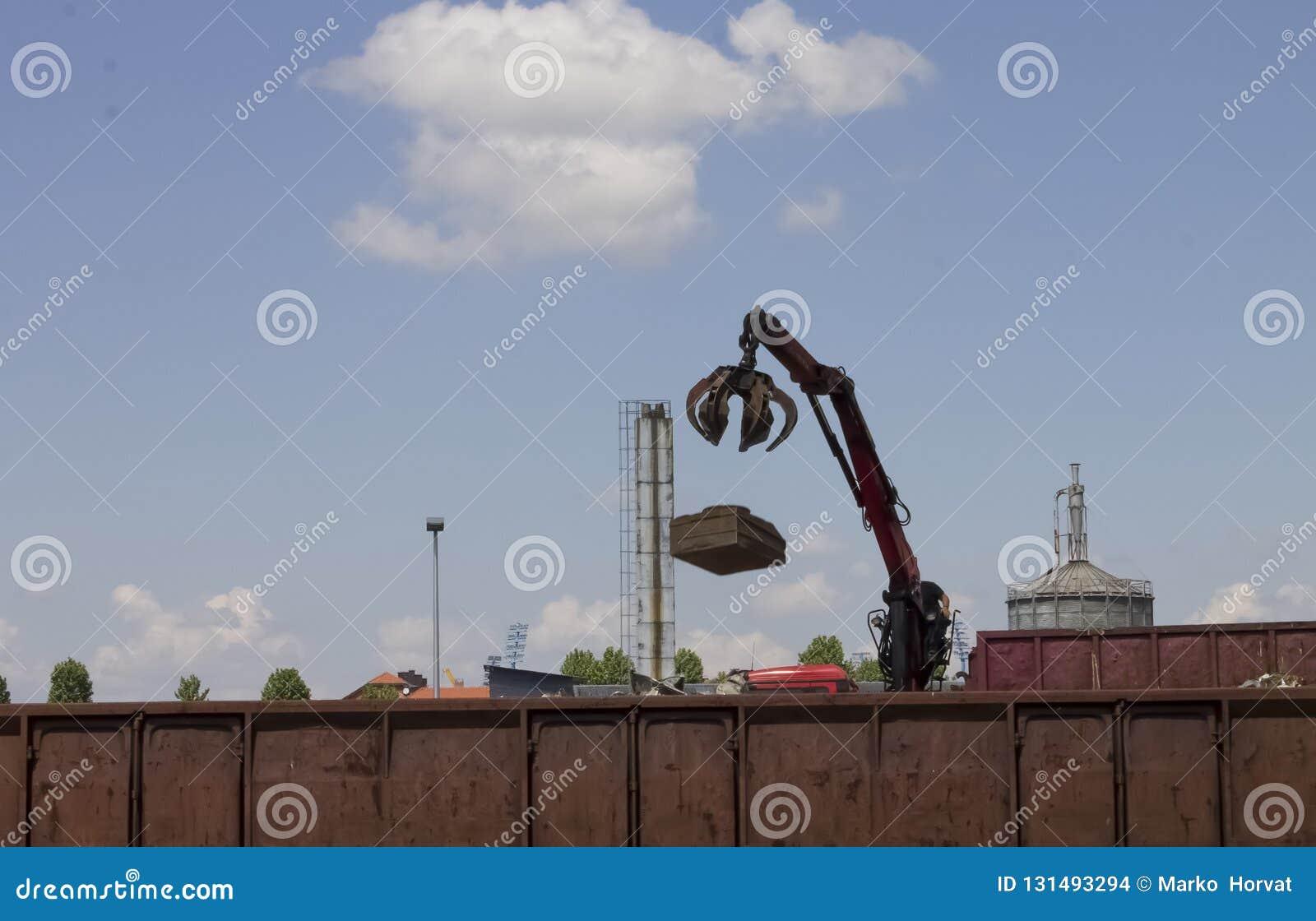 Rifiuti industriali di lancio del metallo della gru rossa in un contenitore del treno alla stazione ferroviaria |camino