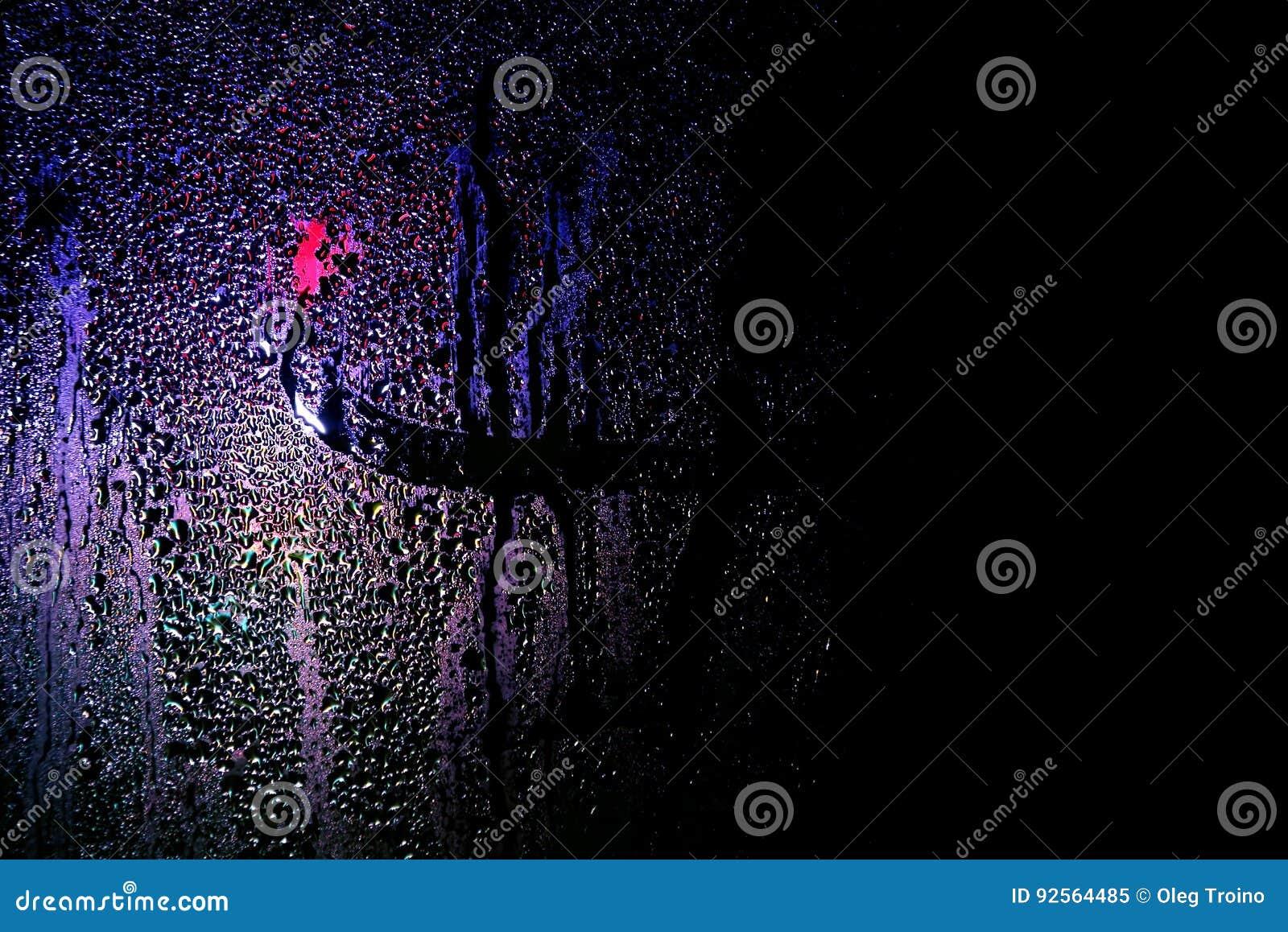 Riflessione della luce notturna su vetro bagnato