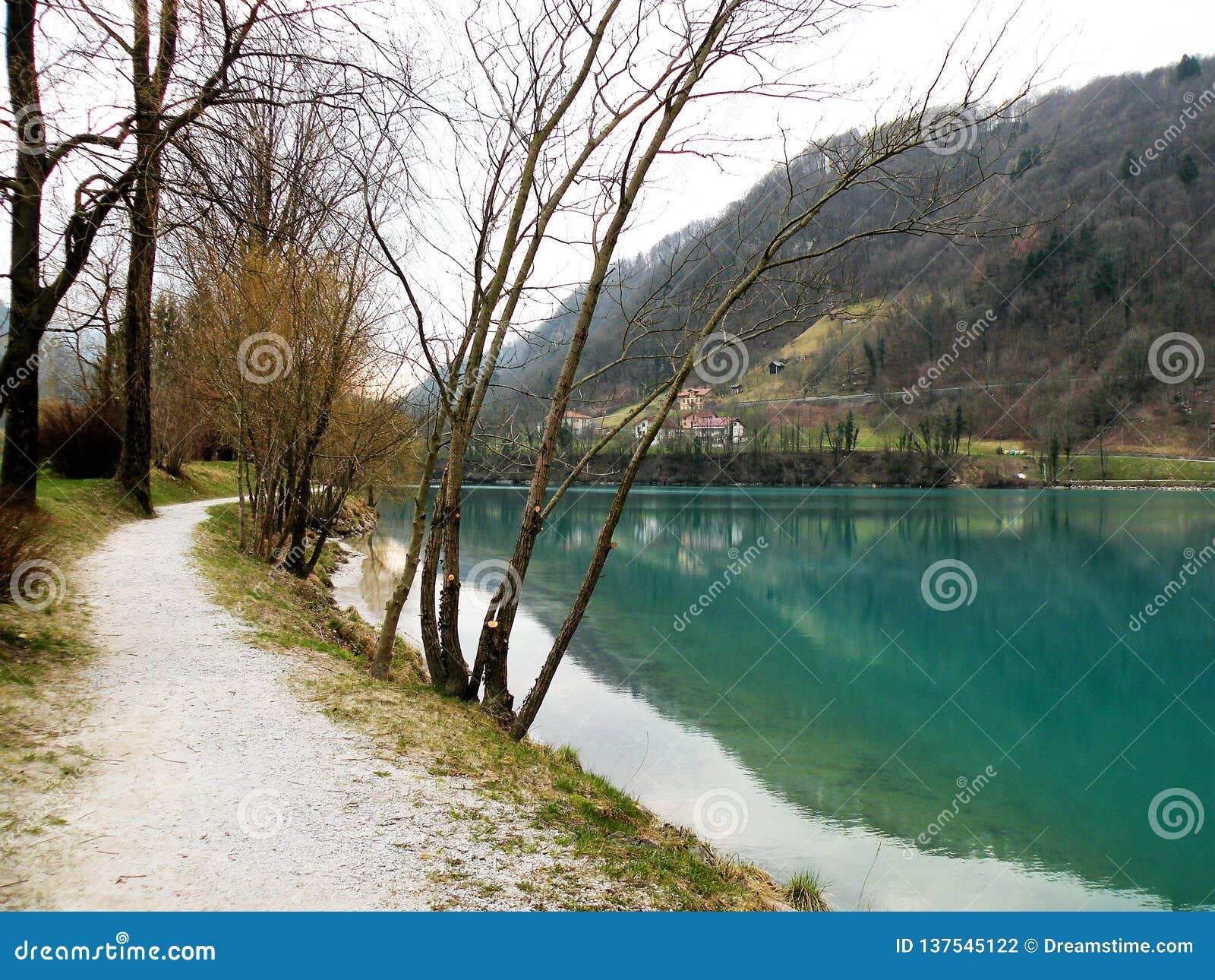 Riflessione delle colline e villaggio e cielo in acqua del turquise