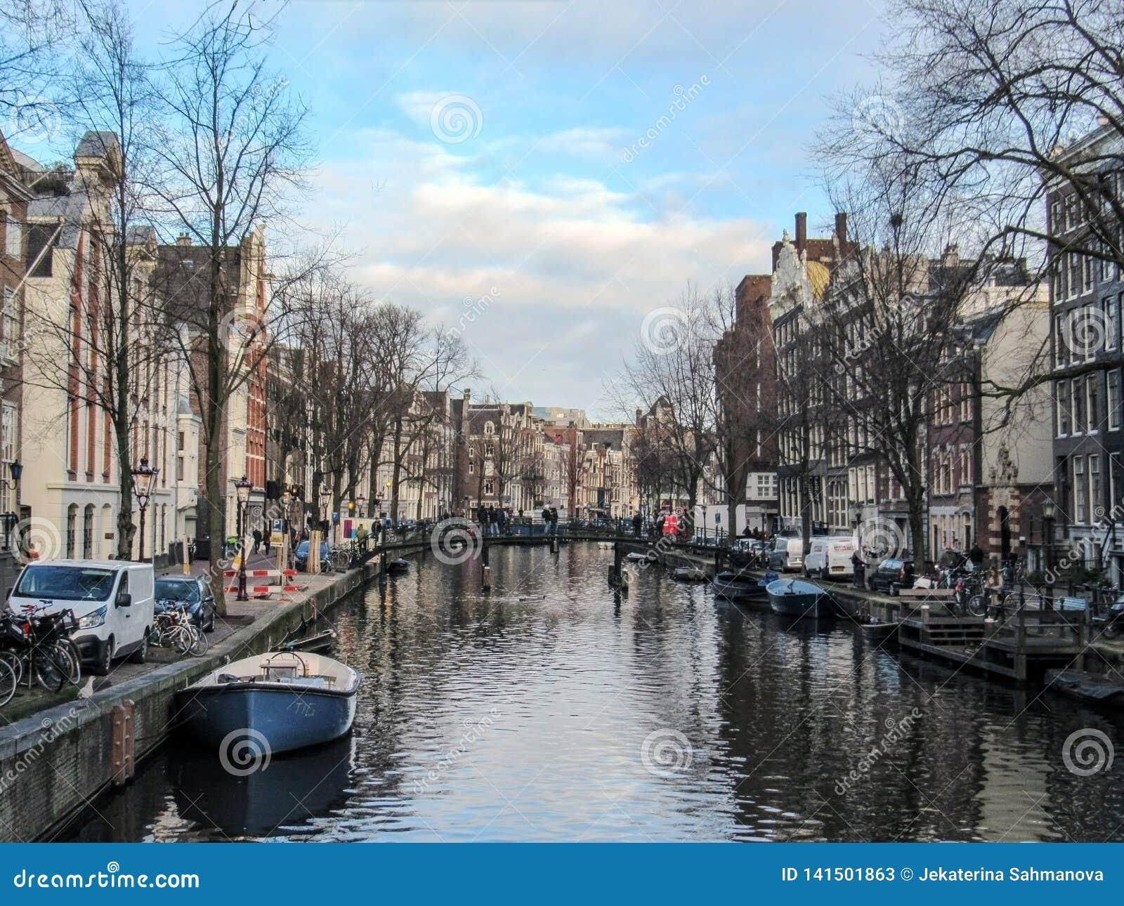 Riflessione delle costruzioni di mattone fiamminghe tradizionali del duch famoso di Amsterdam sul canale in Olanda, Paesi Bassi