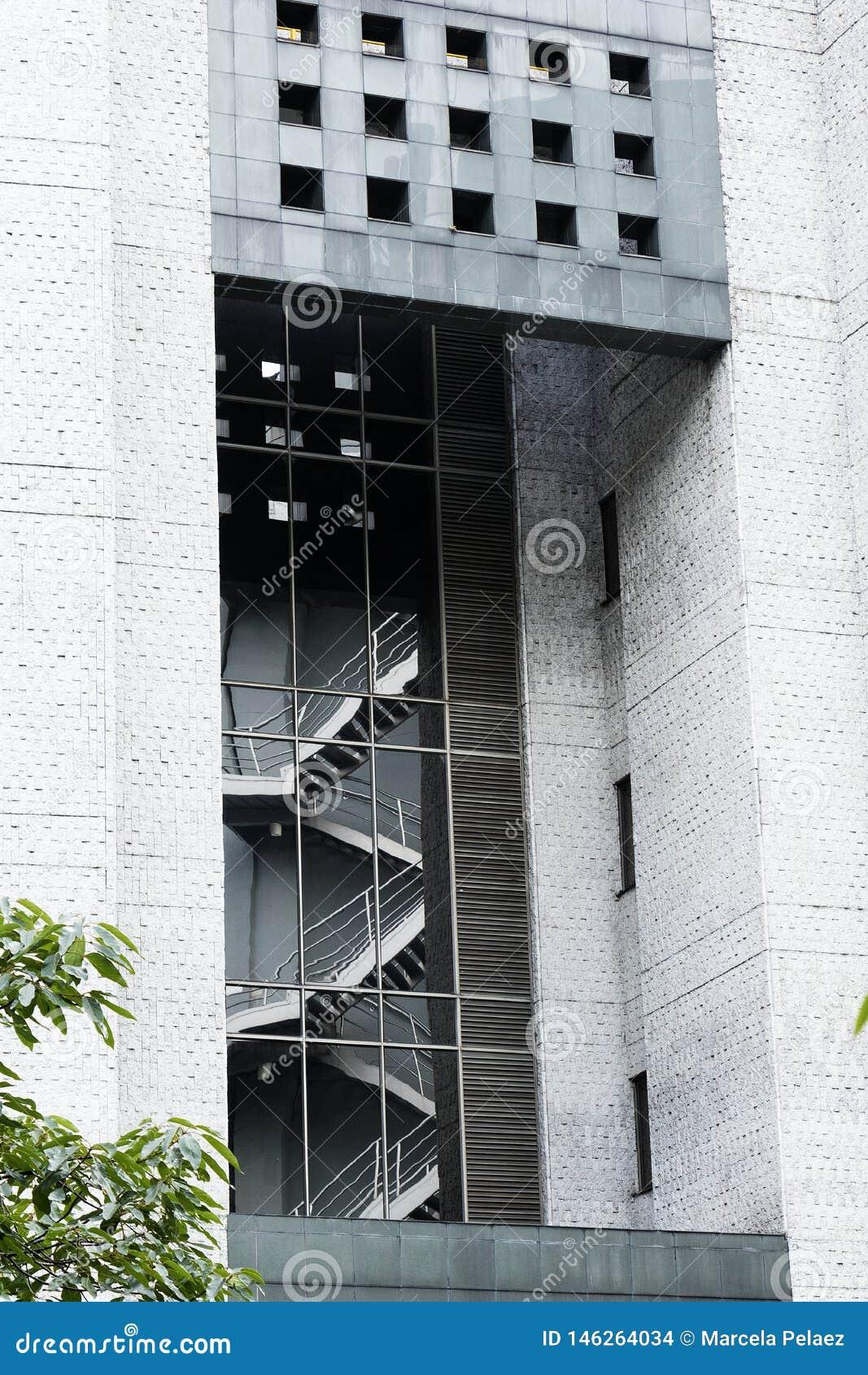 Riflessione delle scale di emergenza nel vetro di una costruzione moderna con le pareti grige del cemento
