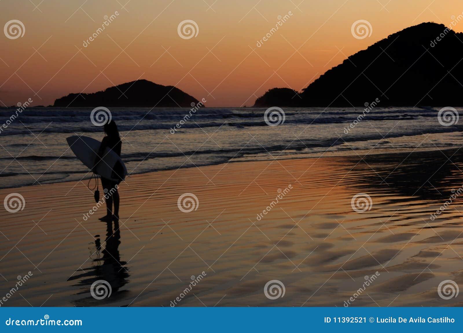 Riflessione di tramonto e del surfista ad una spiaggia tropicale