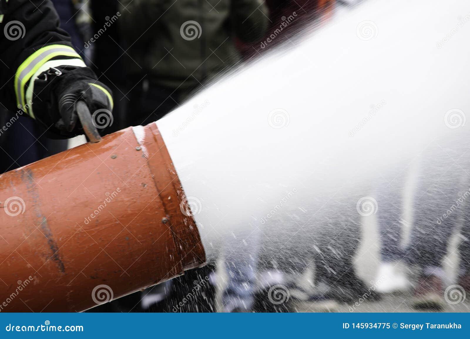 Rifornimento di schiuma da un estintore, mosche estinguenti della schiuma dall estintore, che tiene il vigile del fuoco nel comba