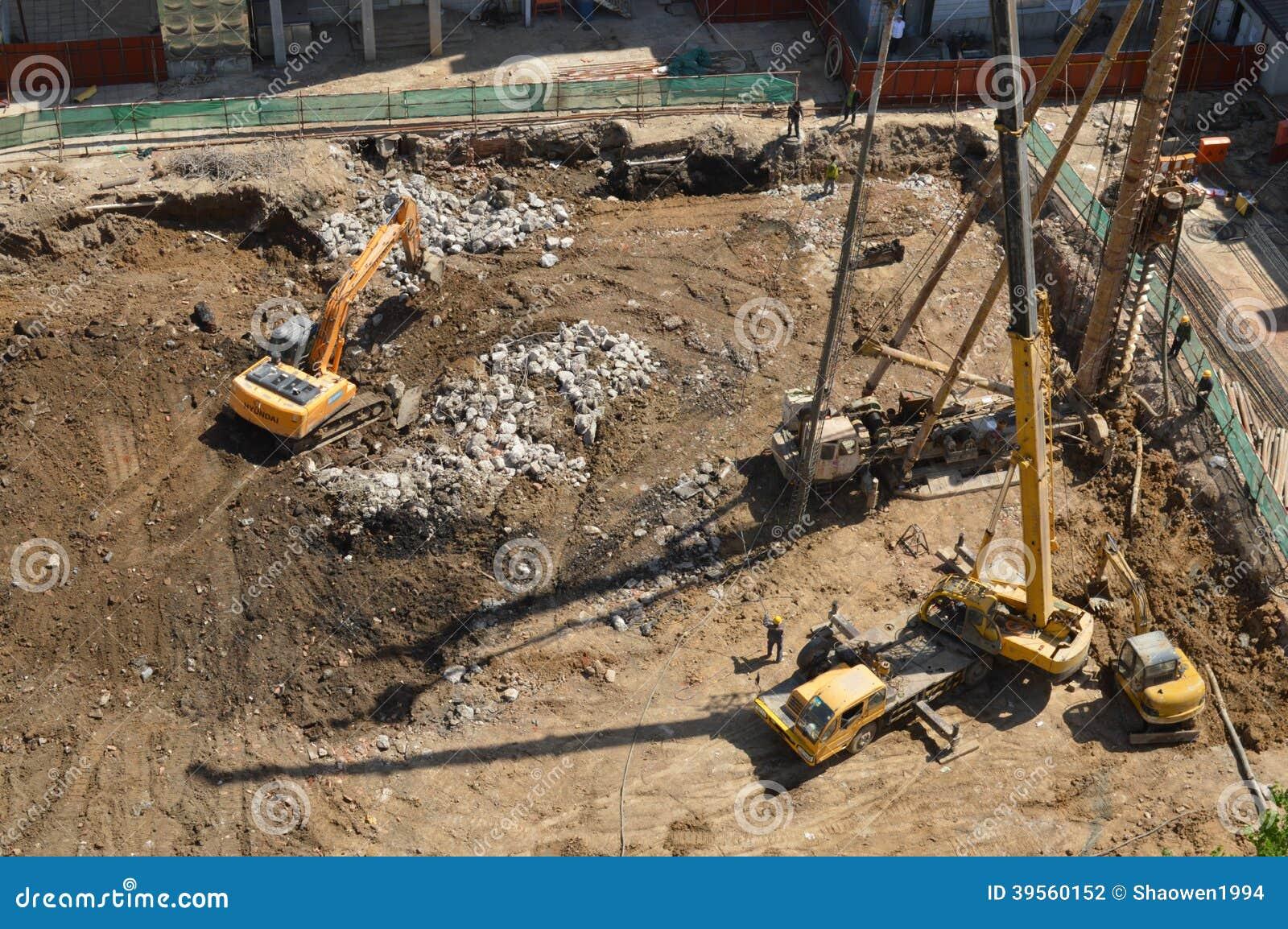 Rig Construction och Backhoe som gräver maskinen