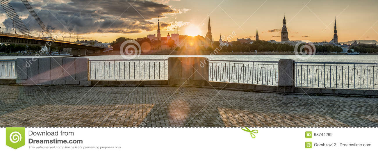 Sunrise on embankment of Daugava river and view on old city of Riga