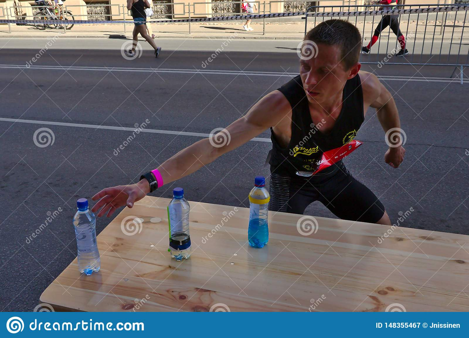 Riga, Latvia - May 19 2019: Caucasian Elite runner Tommy searching for sports drink