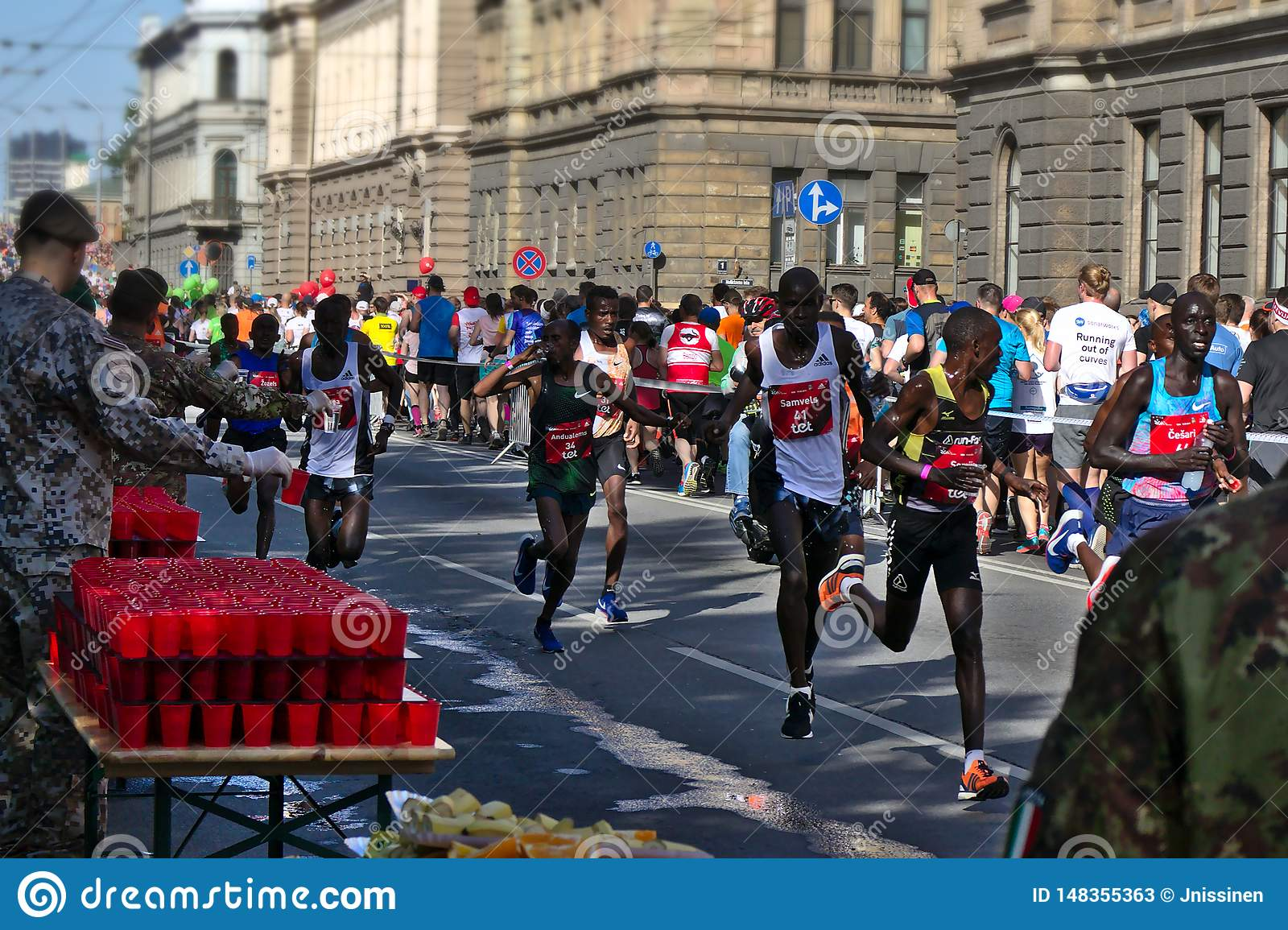 Riga, Latvia - May 19 2019: Elite male Runners passing refreshment point exhausted