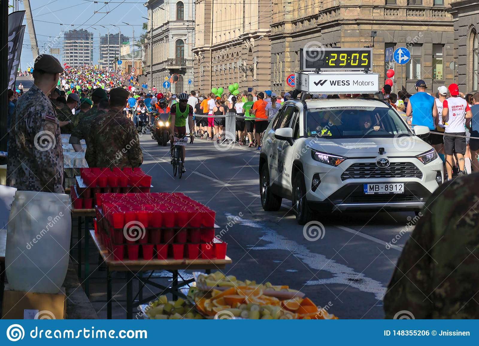 Riga, Latvia - May 19 2019: First Elite runners approaching refreshment station behind chase car