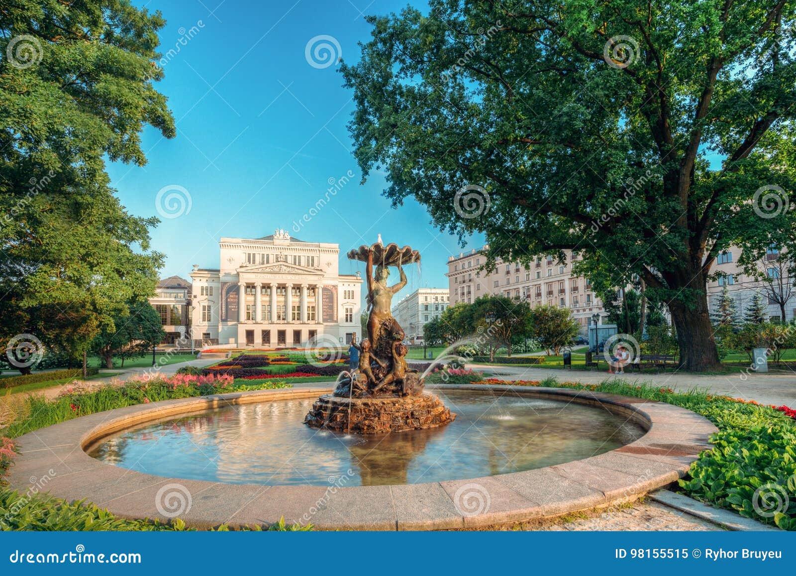Riga, Latvia A ninfa da fonte na água espirra o bulevar de Aspazijas perto do teatro da ópera nacional