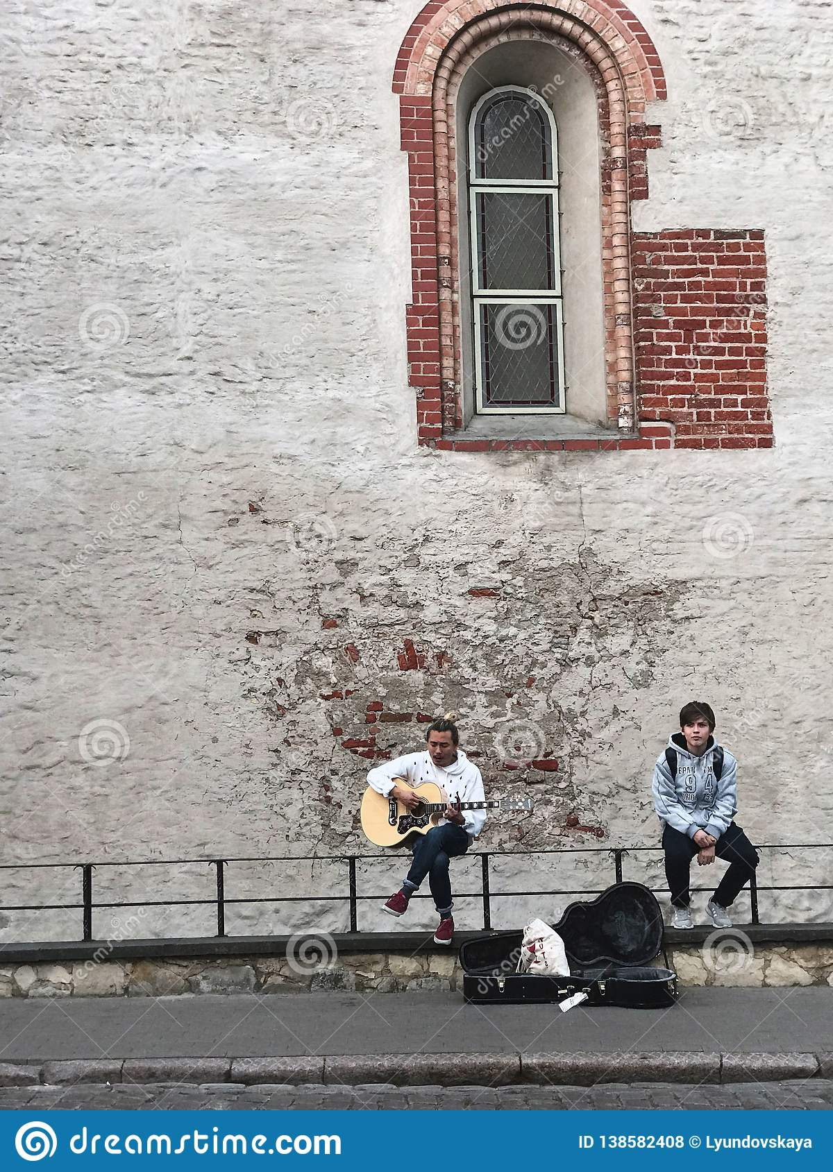 Riga, Latvia, September 18, 2018. One guy plays the guitar and sings a romantic song, the second one listens. Near the case from
