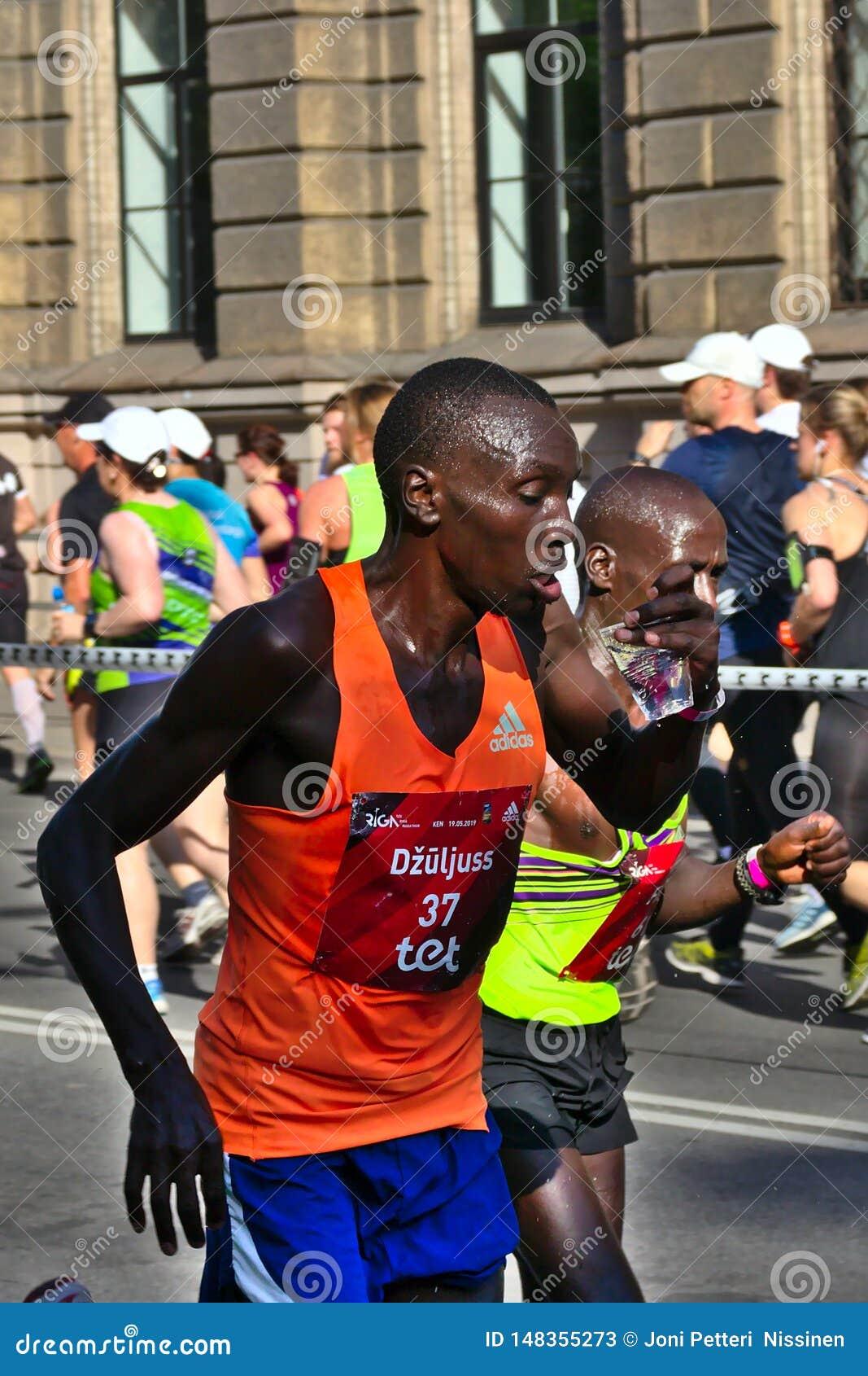 Riga, Let?nia - 19 de maio de 2019: Close up do corredor masculino Julius da elite que toma o sorvo da ?gua