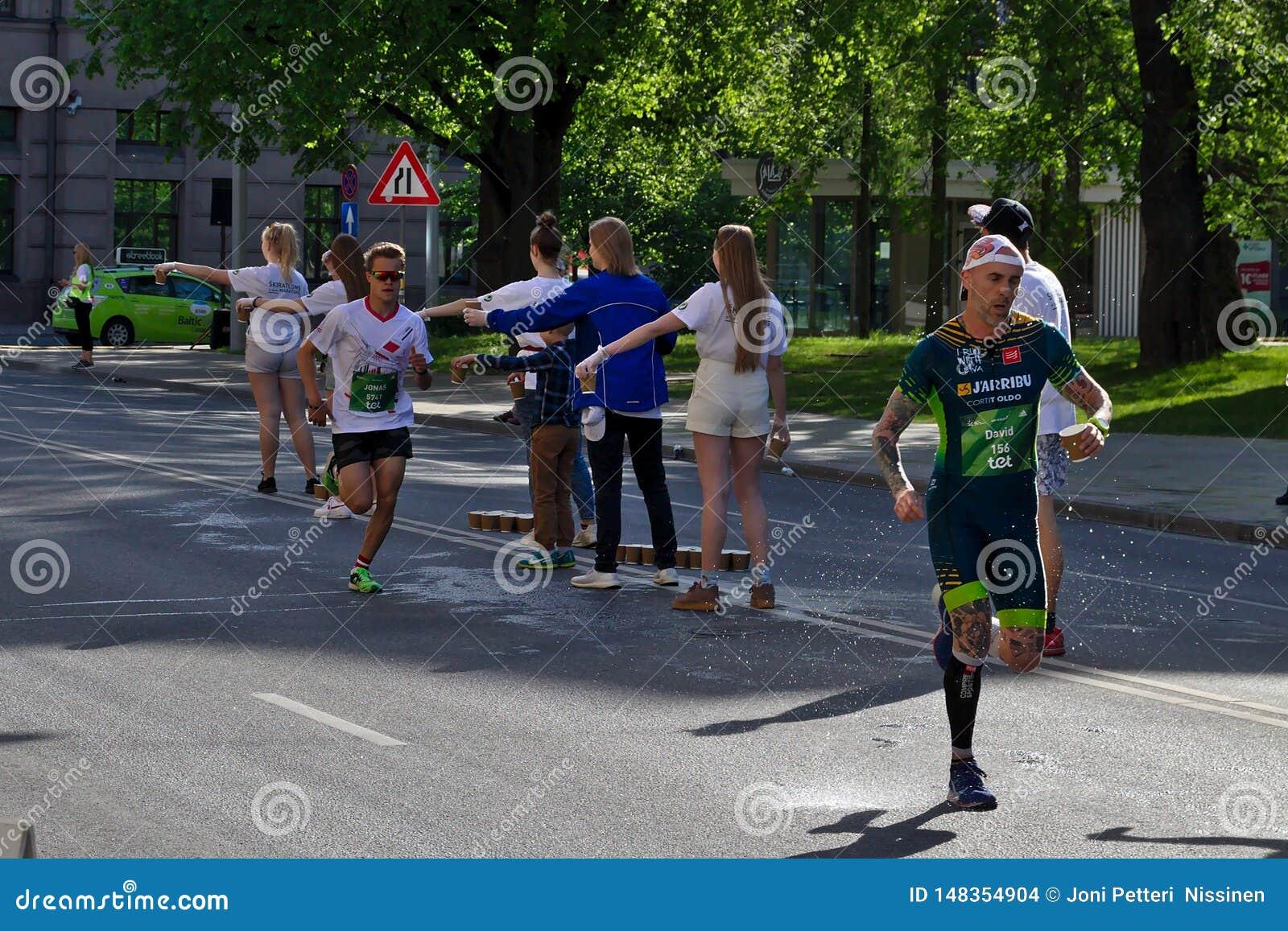 Riga, Let?nia - 19 de maio de 2019: Os corredores os mais r?pidos que chegam ao primeiro ponto do rafrescamento