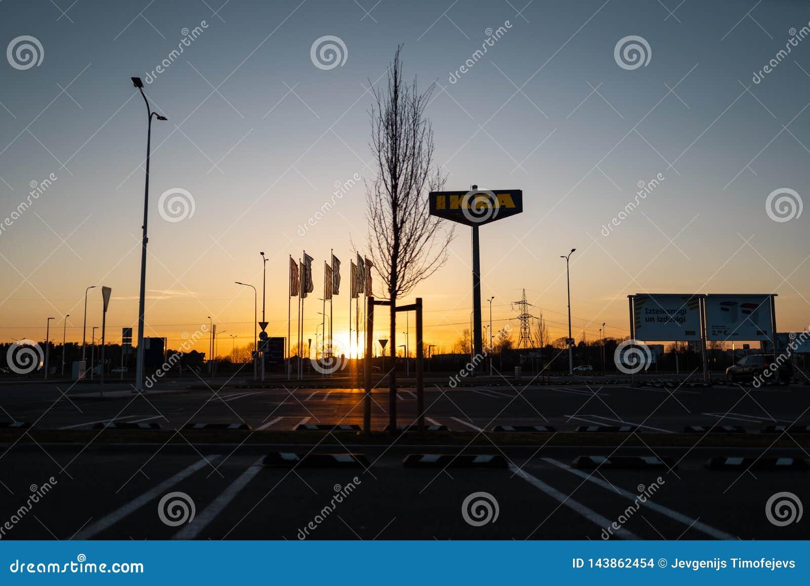 RIGA, LET?NIA - 3 DE ABRIL DE 2019: Sinal do tipo de IKEA durante a noite escura e vento - c?u azul no fundo
