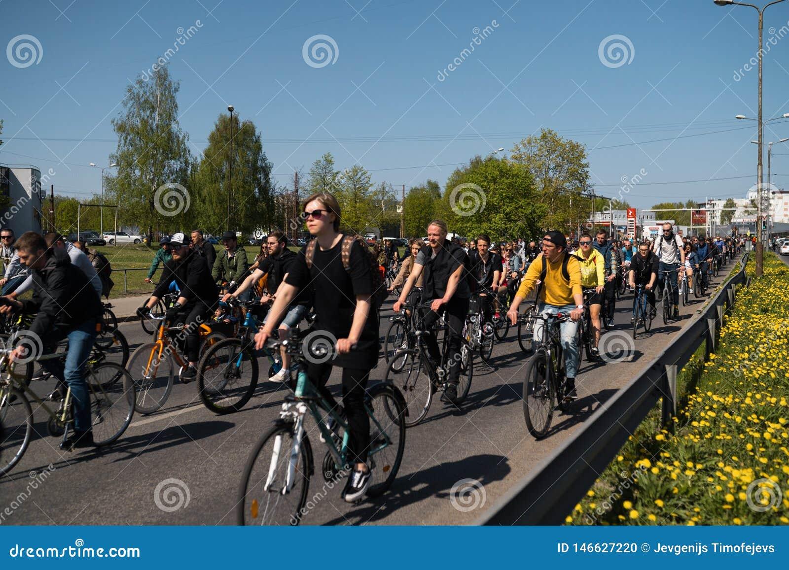 RIGA, LET?NIA - 1? DE MAIO DE 2019: Parada da bicicleta no Dia do Trabalhador com fam?lias e amigos na estrada do espa?o p?blico