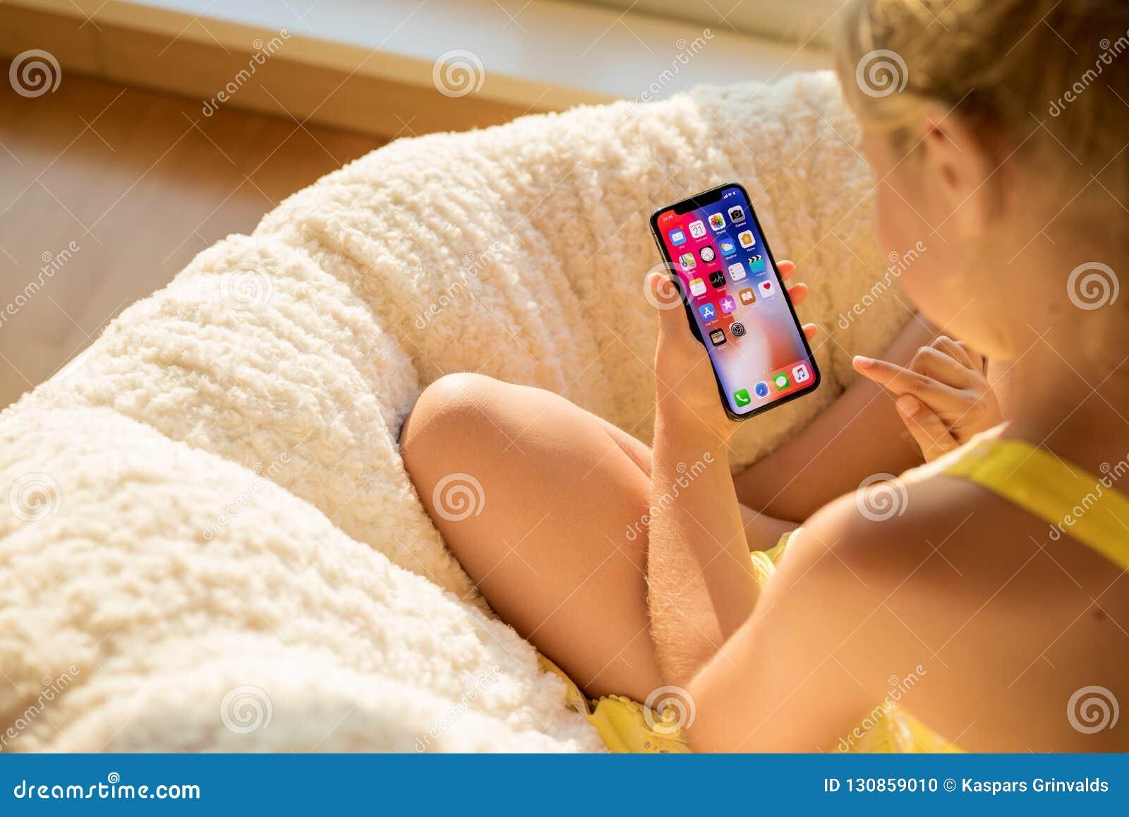 Riga, Letland - Juli 21, 2018: IPhone X van de meisjesholding ter beschikking