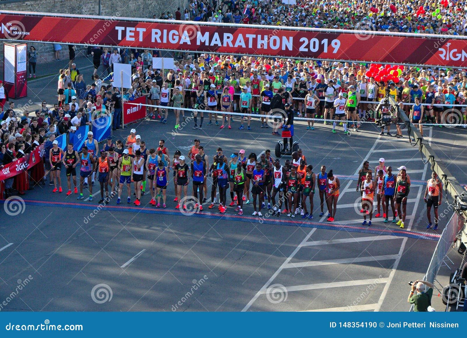 Riga, Letland - Mei 19 2019: Eliteagenten die van de marathon van Riga TET bij de beginlijn een rij vormen