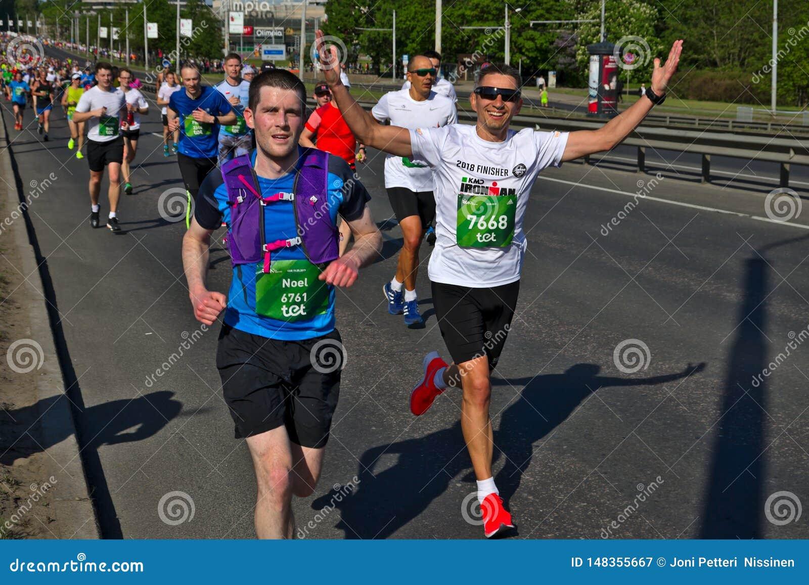 Riga, Letland - Mei 19 2019: Gelukkige Kaukasische de agentenhanden van de merriemarathon omhoog met zonnebril