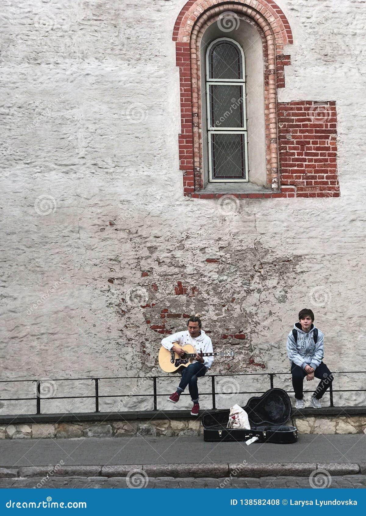 Riga, Letland, 18 September, 2018 Één kerel speelt de gitaar en zingt een romantisch lied, tweede luistert  Dichtbij het geval va