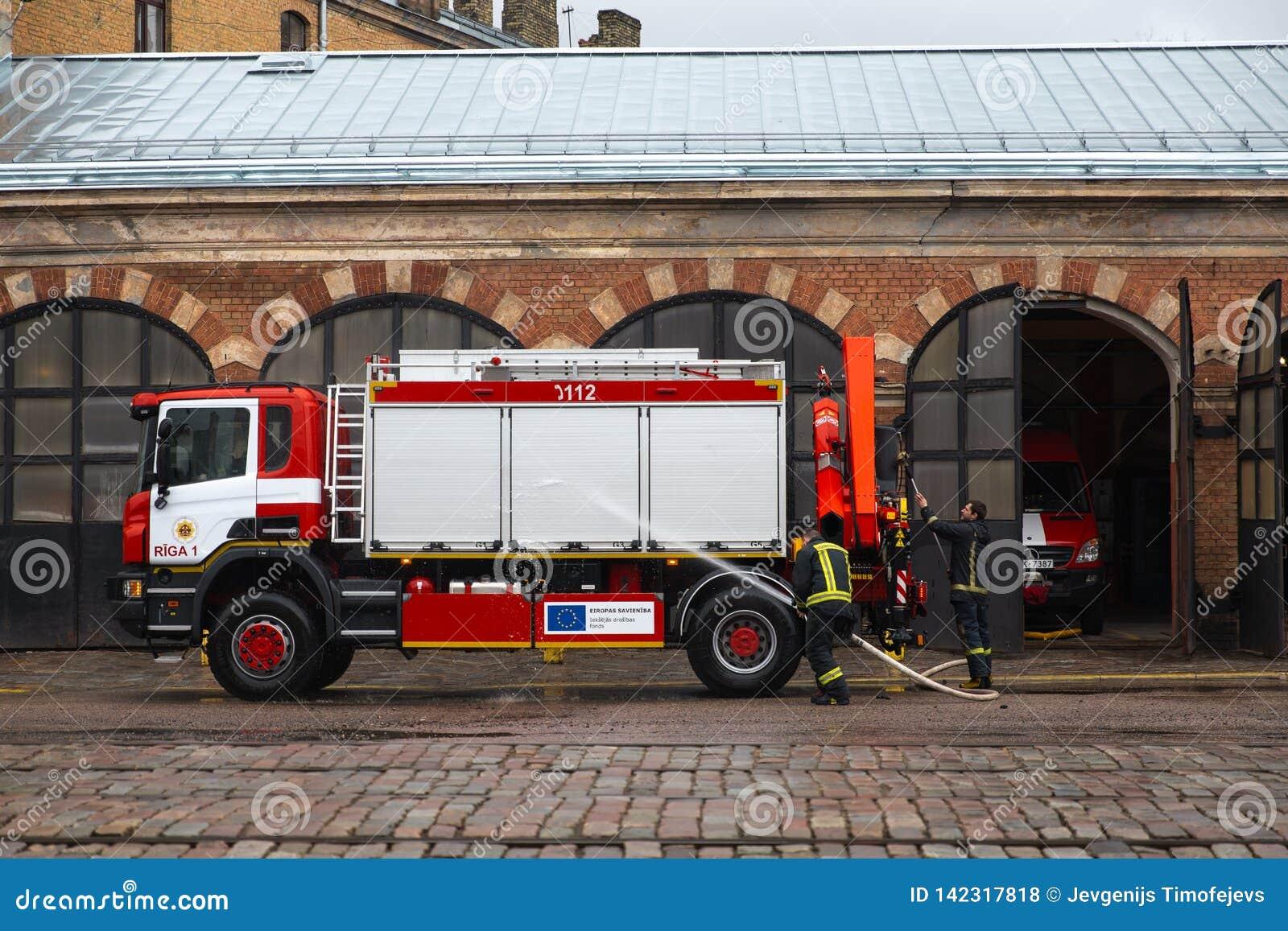 RIGA, LETONIA - 16 DE MARZO DE 2019: Se está limpiando el coche de bomberos - el conductor lava el camión del bombero en un depo