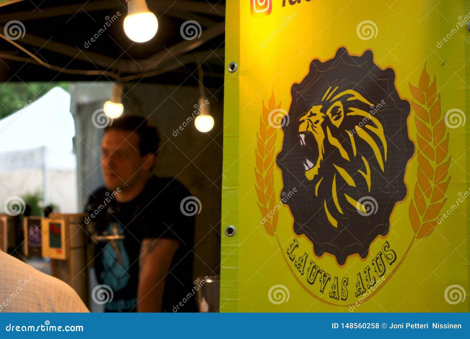 Riga, Letonia - 24 de mayo de 2019: Camarero del orden siguiente que espera de la cerveza de Lauvas