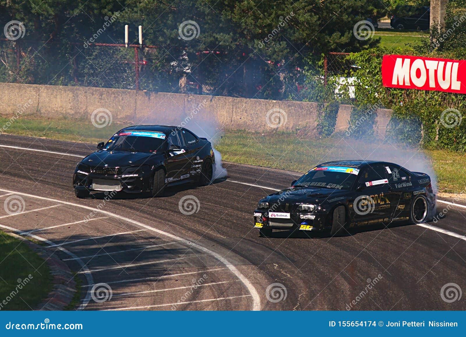 Riga Lettland - Augusti 02, 2019 - två BMW som driver till och med första hörn av spåret