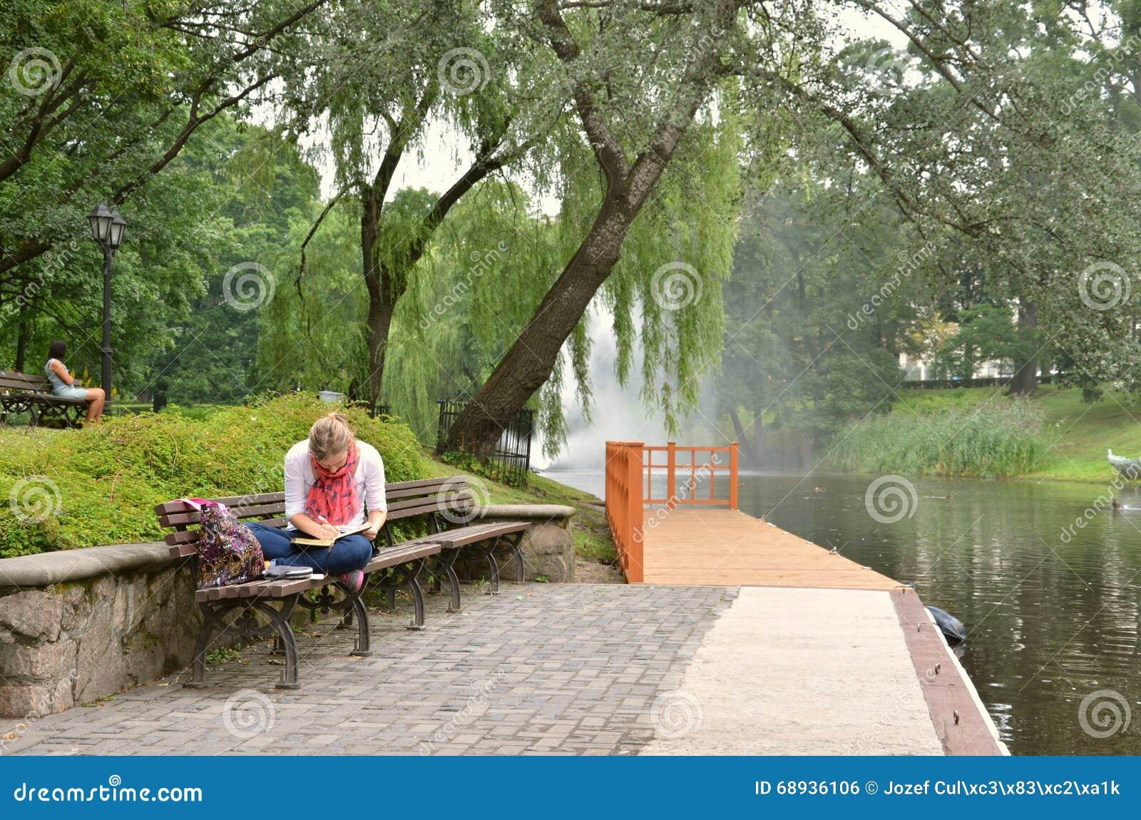 RIGA/LETTLAND - Juli 27, 2013: Den unga kvinnan skriver något i hennes anteckningsbok på flodbanken i stad parkerar av Riga