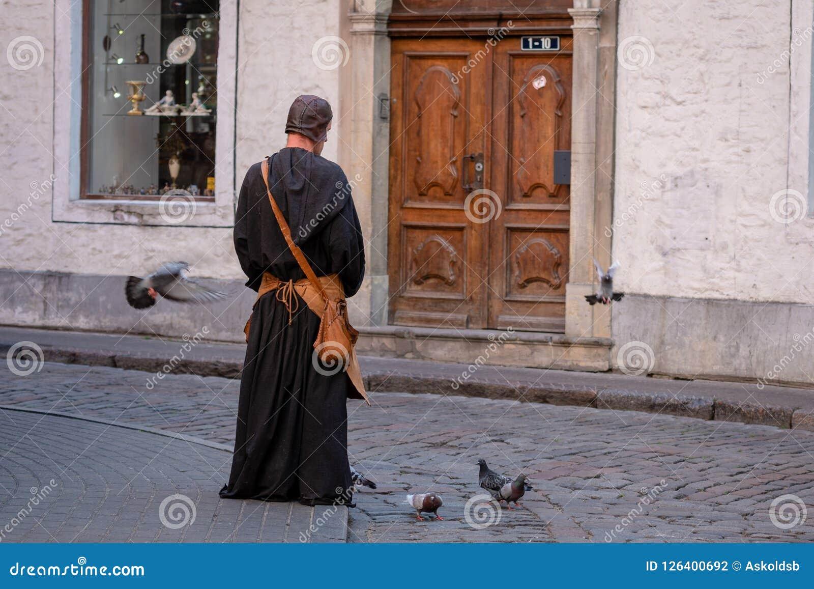 RIGA, LETTLAND - 31. JULI 2018: Mann in der mittelalterlichen Kleidung in der alten Stadt auf der Straße zieht die Tauben ein