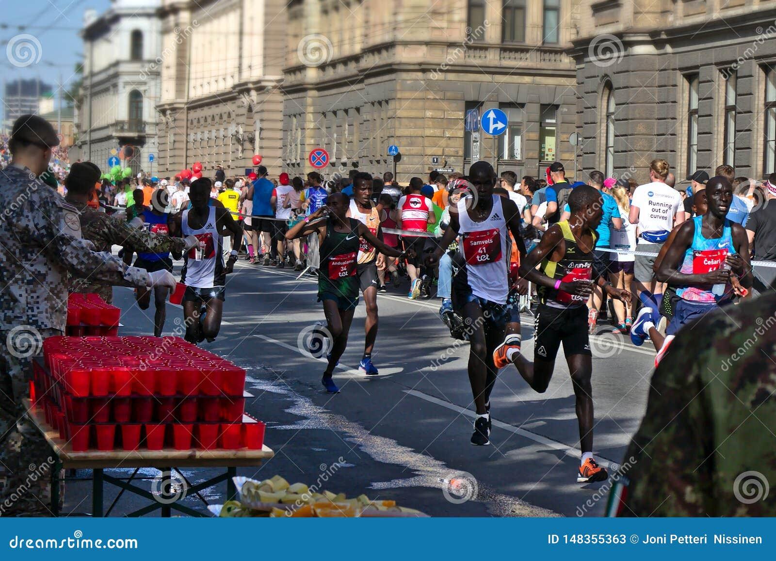 Riga, Lettland - 19. Mai 2019: Auslese-männliche Läufer, die den Erfrischungspunkt erschöpft führen
