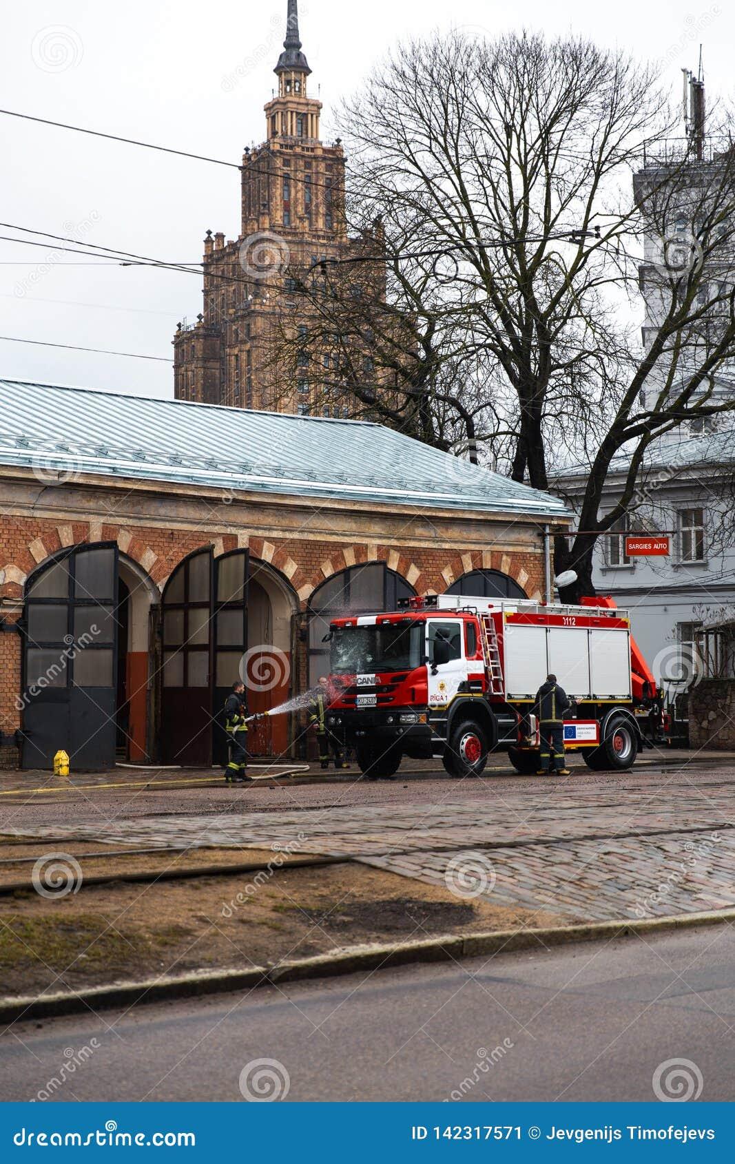 RIGA LETTLAND - MARS 16, 2019: Brandlastbilen är den rengjorda - chauffören tvättar brandmanlastbilen på en depo - sceniska sikte