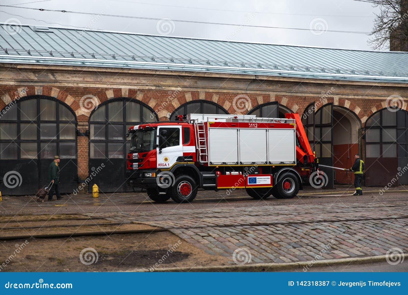 RIGA LETTLAND - MARS 16, 2019: Brandlastbilen är rengjort - chauffören tvättar brandmanlastbilen på en depo - passera för gamal m