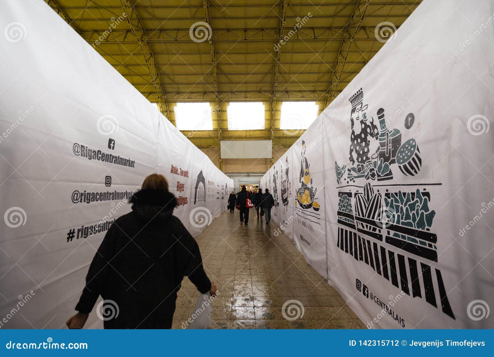 RIGA LETTLAND - MARS 16, 2019: Paviljong Riga för central marknad under konstruktion, folk som förbigår - tidigare zeppelinare
