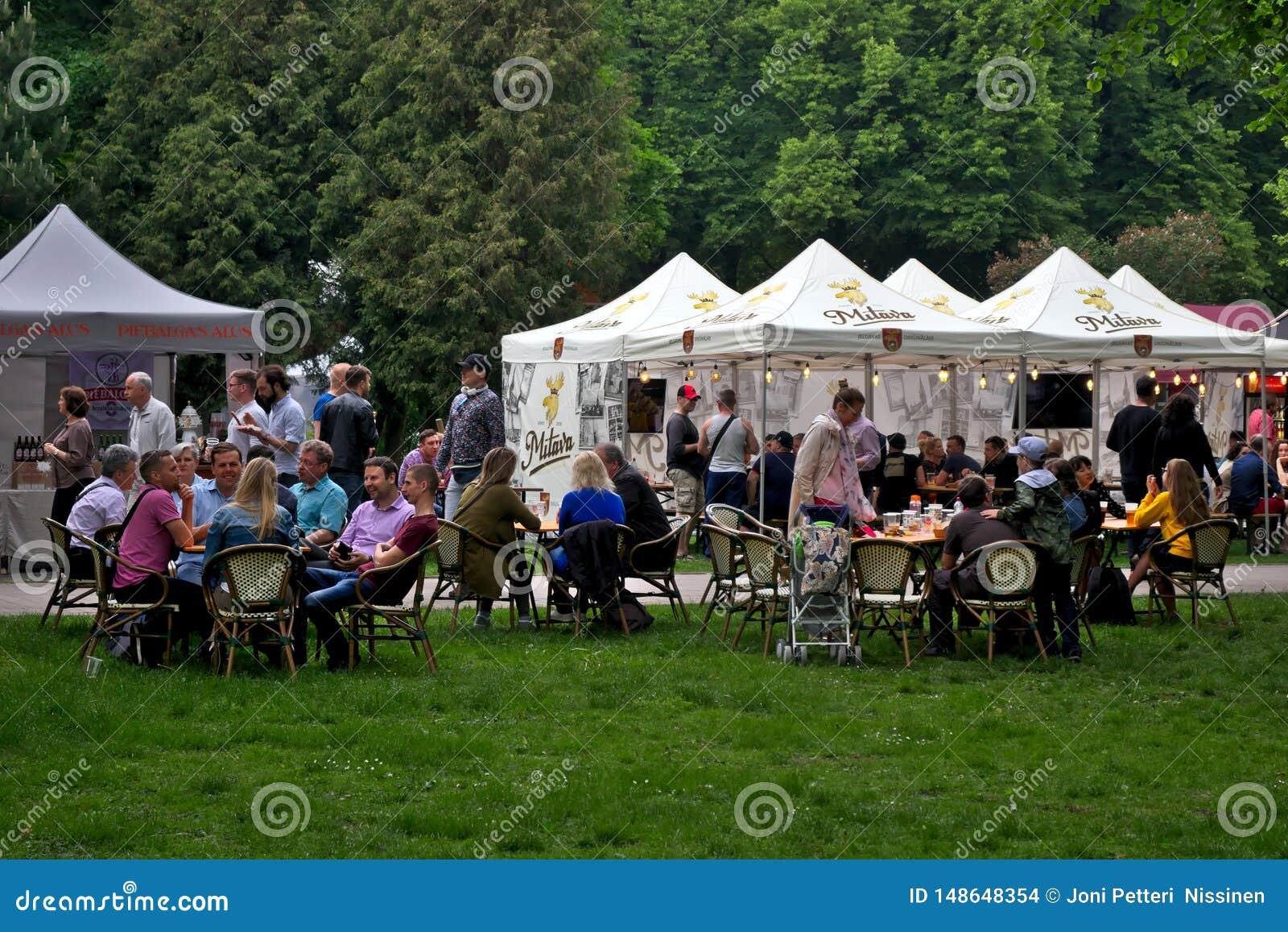 Riga, Lettonia - 24 maggio 2019 - la gente che gode delle bevande che sorridono nel parco dei vermanes