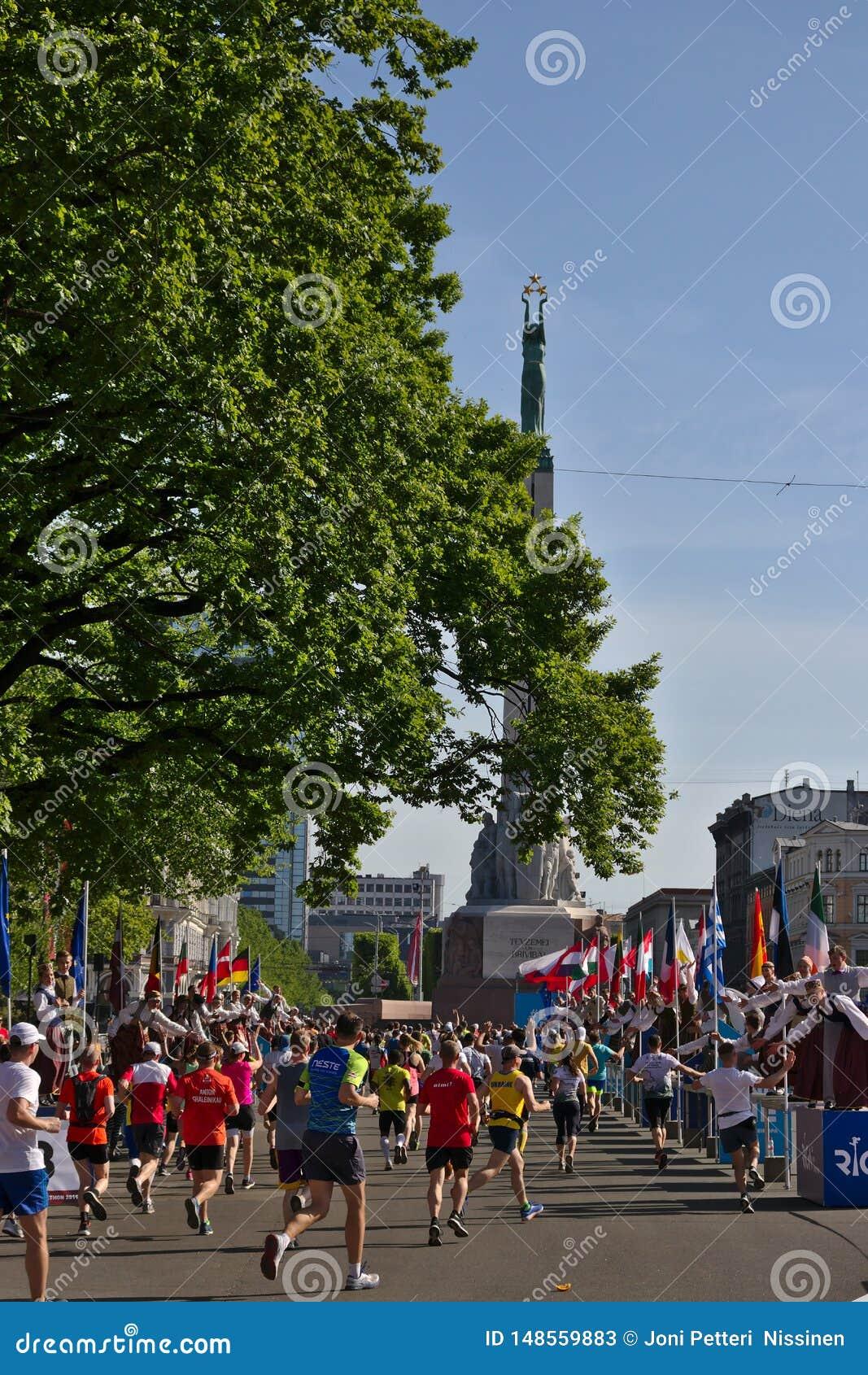 Riga, Lettonie - 19 mai 2019 : Les marathoniens atteignant la statue de libert? avec les majorettes traditionnellement v?tues don