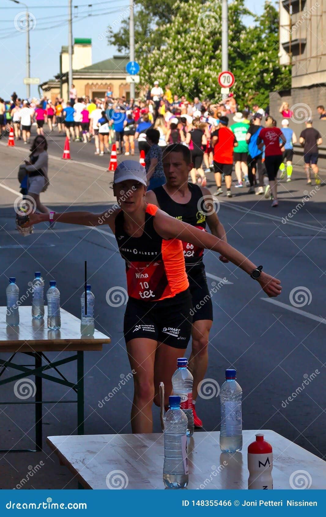 Riga, Lettonie - 19 mai 2019 : Les sports de saisie de coureur femelle caucasien d ?lite boivent avec la grande vitesse